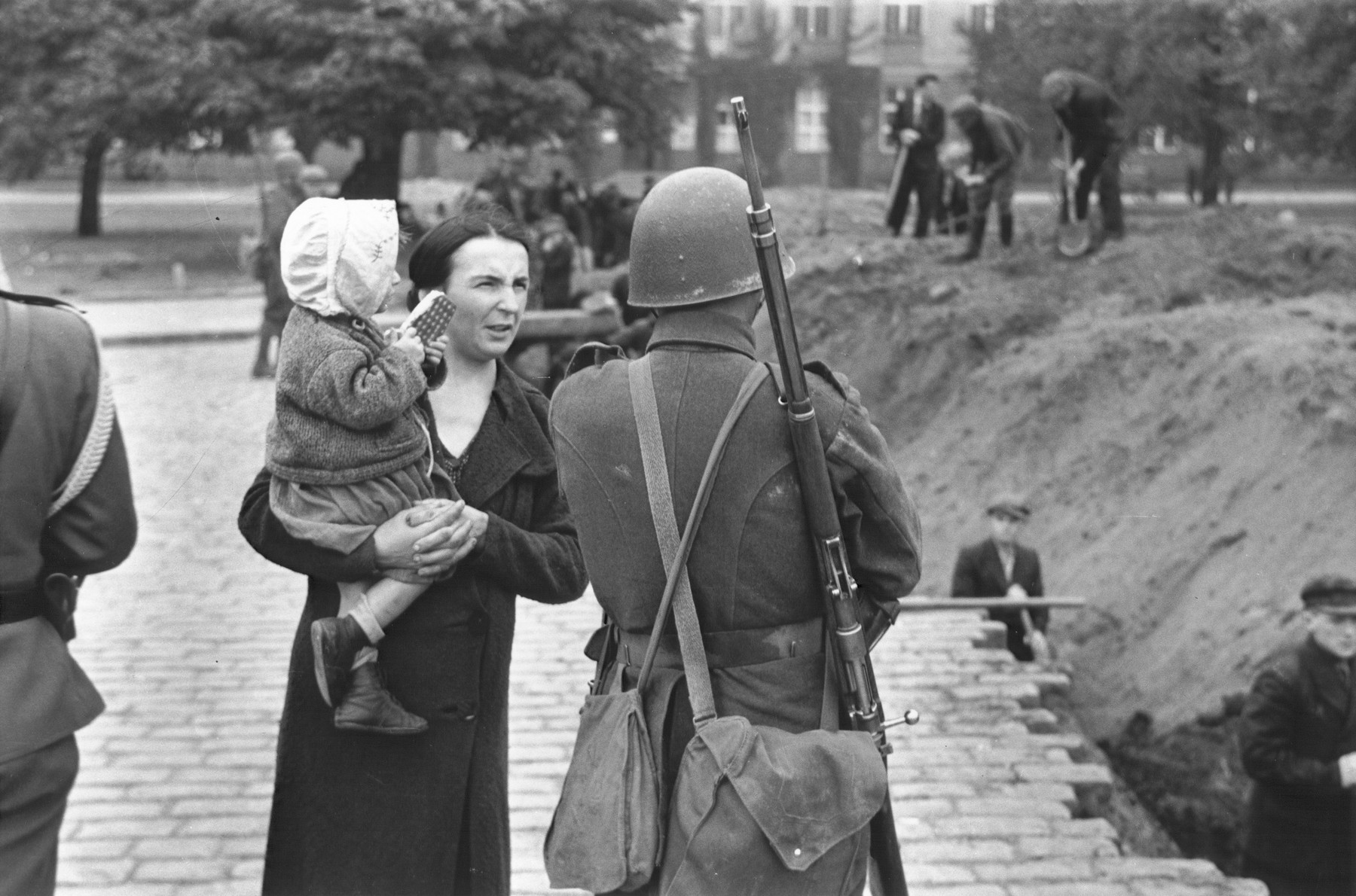 A Polish woman holding her child converses with her soldier husband, who supervises a group of civilians digging an anti-tank trench along a street in Warsaw to slow the advance of the German army.