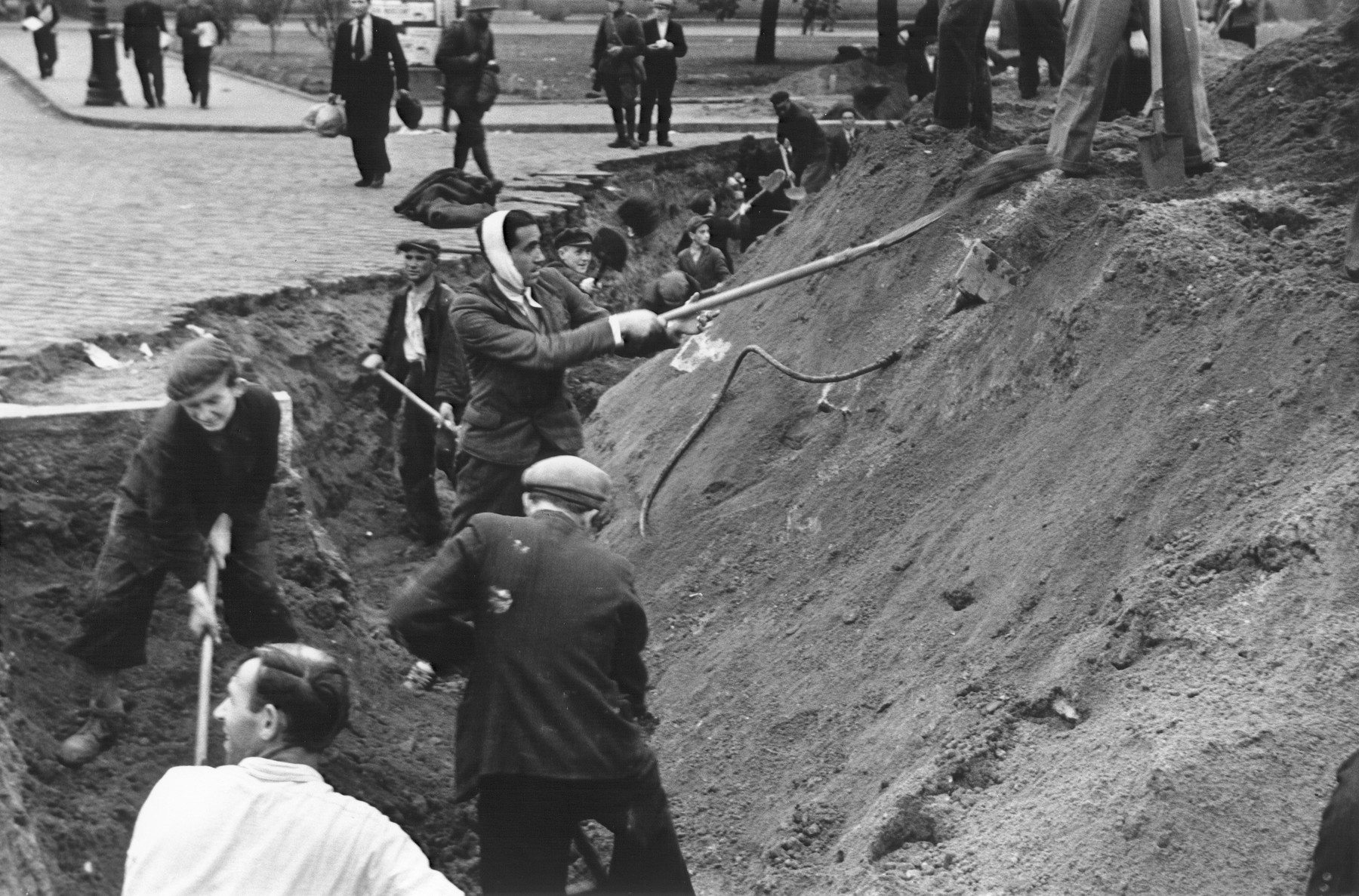 Polish civilians dig an anti-tank trench and plant street car rails in the ground on a street in Warsaw to slow the advance of the German army.