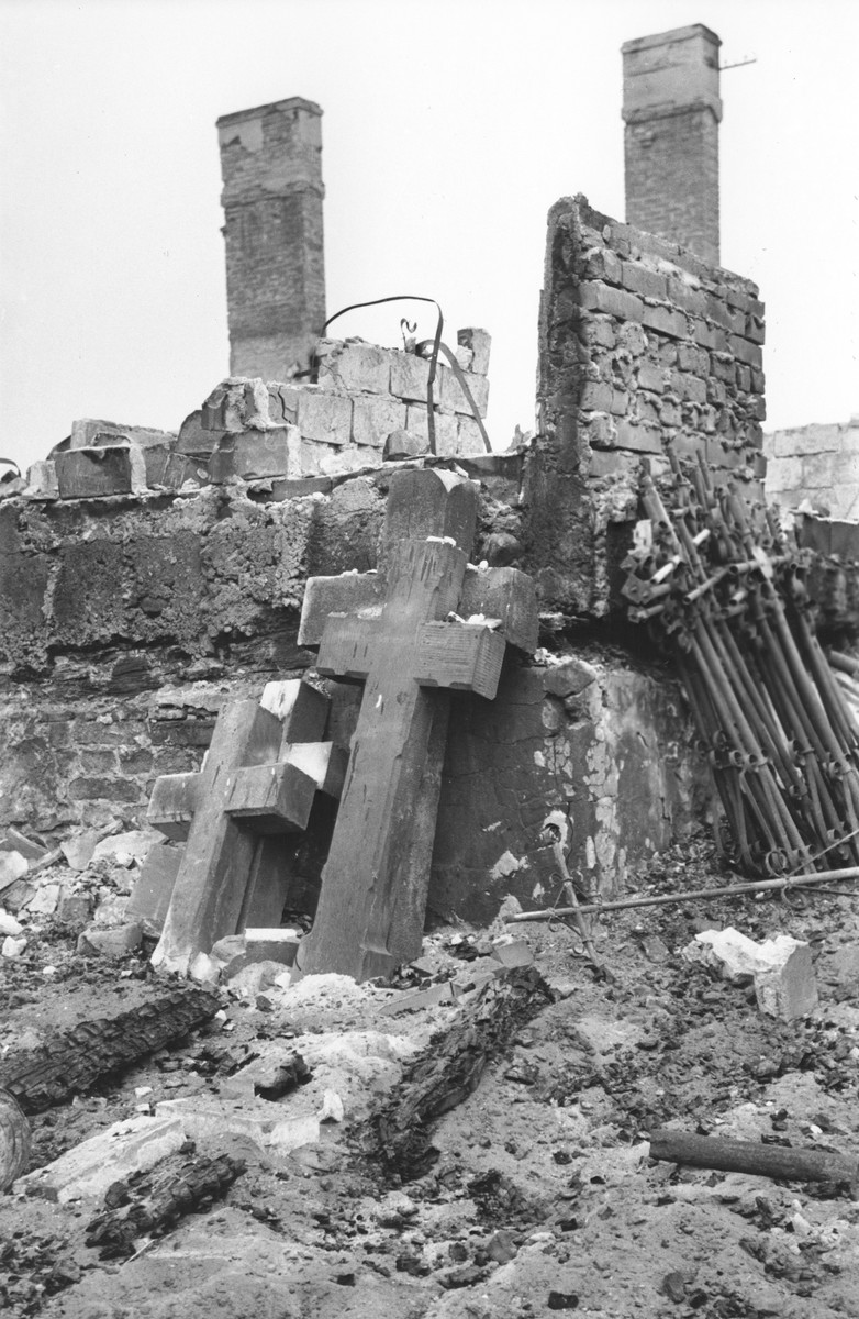 Stacks of crucifixes lie against the brick wall of a destroyed church or cemetery structure in Warsaw.