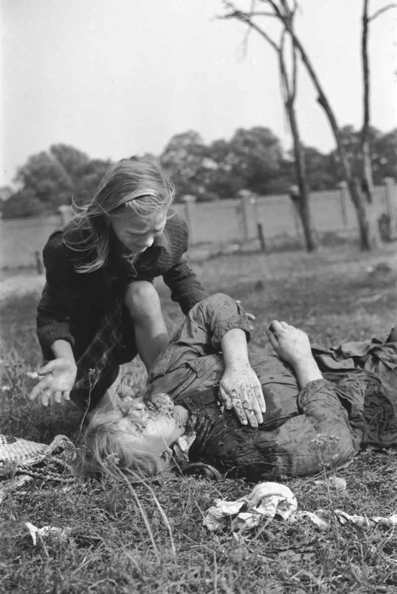 """A ten-year-old Polish girl named Kazimiera Mika, mourns the death of her older sister, who was killed in a field in Warsaw during a German air raid.  In the words of photographer Julien Bryan, """"As we drove by a small field at the edge of town we were just a few minutes too late to witness a tragic event, the most incredible of all.  Seven women had been digging potatoes in a field.  There was no flour in their district, and they were desperate for food.  Suddenly two German planes appeared from nowhere and dropped two bombs only two hundred yards away on a small home.  Two women in the house were killed.  The potato diggers dropped flat upon the ground, hoping to be unnoticed.  After the bombers had gone, the women returned to their work.  They had to have food.  But the Nazi fliers were not satisfied with their work.  In a few minutes they came back and swooped down to within two hundred feet of the ground, this time raking the field with machine-gun fire.  Two of the seven women were killed.  The other five escaped somehow.  While I was photographing the bodies, a little ten-year old girl came running up and stood transfixed by one of the dead.  The woman was her older sister.  The child had never before seen death and couldn't understand why her sister would not speak to her...  The child looked at us in bewilderment.  I threw my arm about her and held her tightly, trying to comfort her.  She cried.  So did I and the two Polish officers who were with me...""""  [Source: Bryan, Julien. """"Warsaw: 1939 Siege; 1959 Warsaw Revisited."""" Warsaw, Polonia, 1959, pp.20-21.]"""