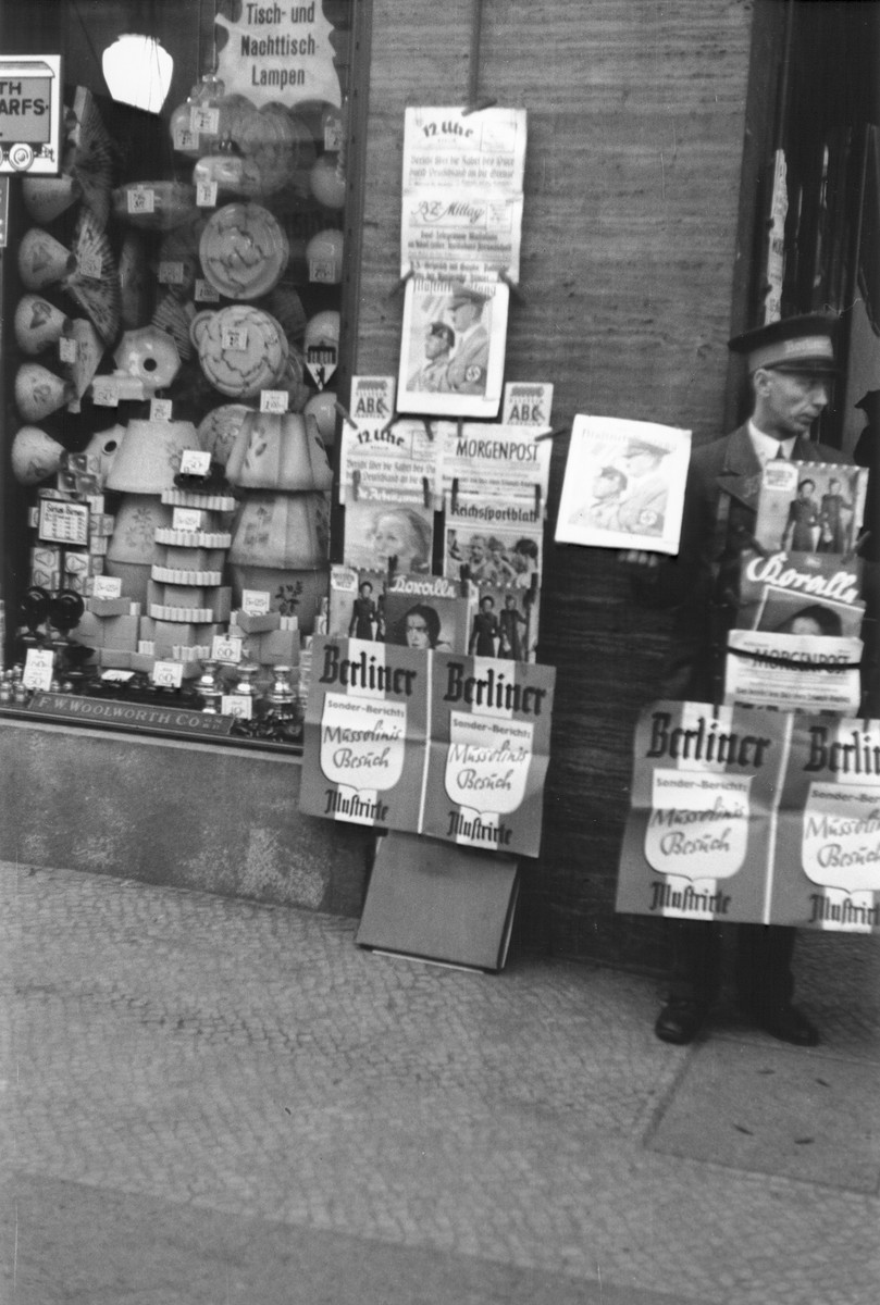 A newspaper vendor stands next to a display of German newspapers and magazines on a commercial street in Berlin.    The advertisement for the Berliner Illustrirte features coverage of Mussolini's official visit to Berlin in September 1937.