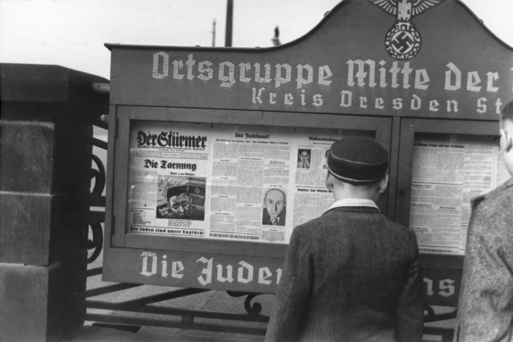 """German boys read an issue of the Stuermer newspaper that is posted in a display box at the entrance to a Nazi party headquarters (Ortsgruppe Mitte der NSDAP) in the Dresden region.  The German slogan at the bottom of the display box reads, """"The Jews are our misfortune."""""""