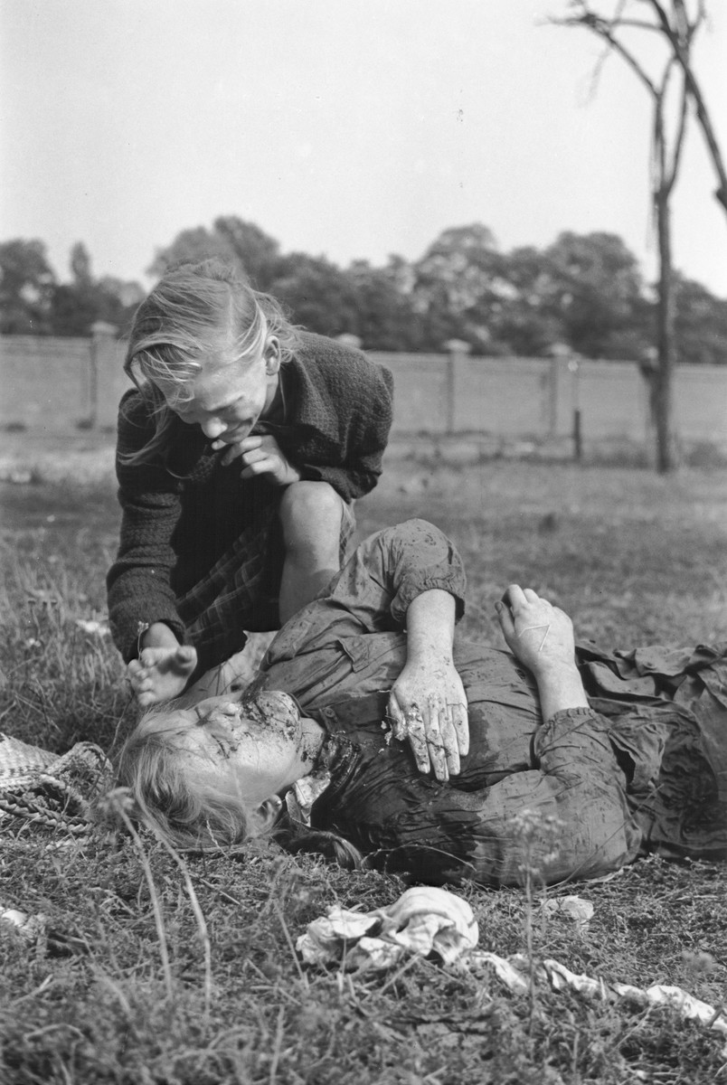 "A ten-year-old Polish girl named Kazimiera Mika, mourns the death of her older sister, who was killed in a field in Warsaw during a German air raid.  In the words of photographer Julien Bryan, ""As we drove by a small field at the edge of town we were just a few minutes too late to witness a tragic event, the most incredible of all.  Seven women had been digging potatoes in a field.  There was no flour in their district, and they were desperate for food.  Suddenly two German planes appeared from nowhere and dropped two bombs only two hundred yards away on a small home.  Two women in the house were killed.  The potato diggers dropped flat upon the ground, hoping to be unnoticed.  After the bombers had gone, the women returned to their work.  They had to have food.  But the Nazi fliers were not satisfied with their work.  In a few minutes they came back and swooped down to within two hundred feet of the ground, this time raking the field with machine-gun fire.  Two of the seven women were killed.  The other five escaped somehow.  While I was photographing the bodies, a little ten-year old girl came running up and stood transfixed by one of the dead.  The woman was her older sister.  The child had never before seen death and couldn't understand why her sister would not speak to her...  The child looked at us in bewilderment.  I threw my arm about her and held her tightly, trying to comfort her.  She cried.  So did I and the two Polish officers who were with me...""  [Source: Bryan, Julien. ""Warsaw: 1939 Siege; 1959 Warsaw Revisited."" Warsaw, Polonia, 1959, pp.20-21.]"