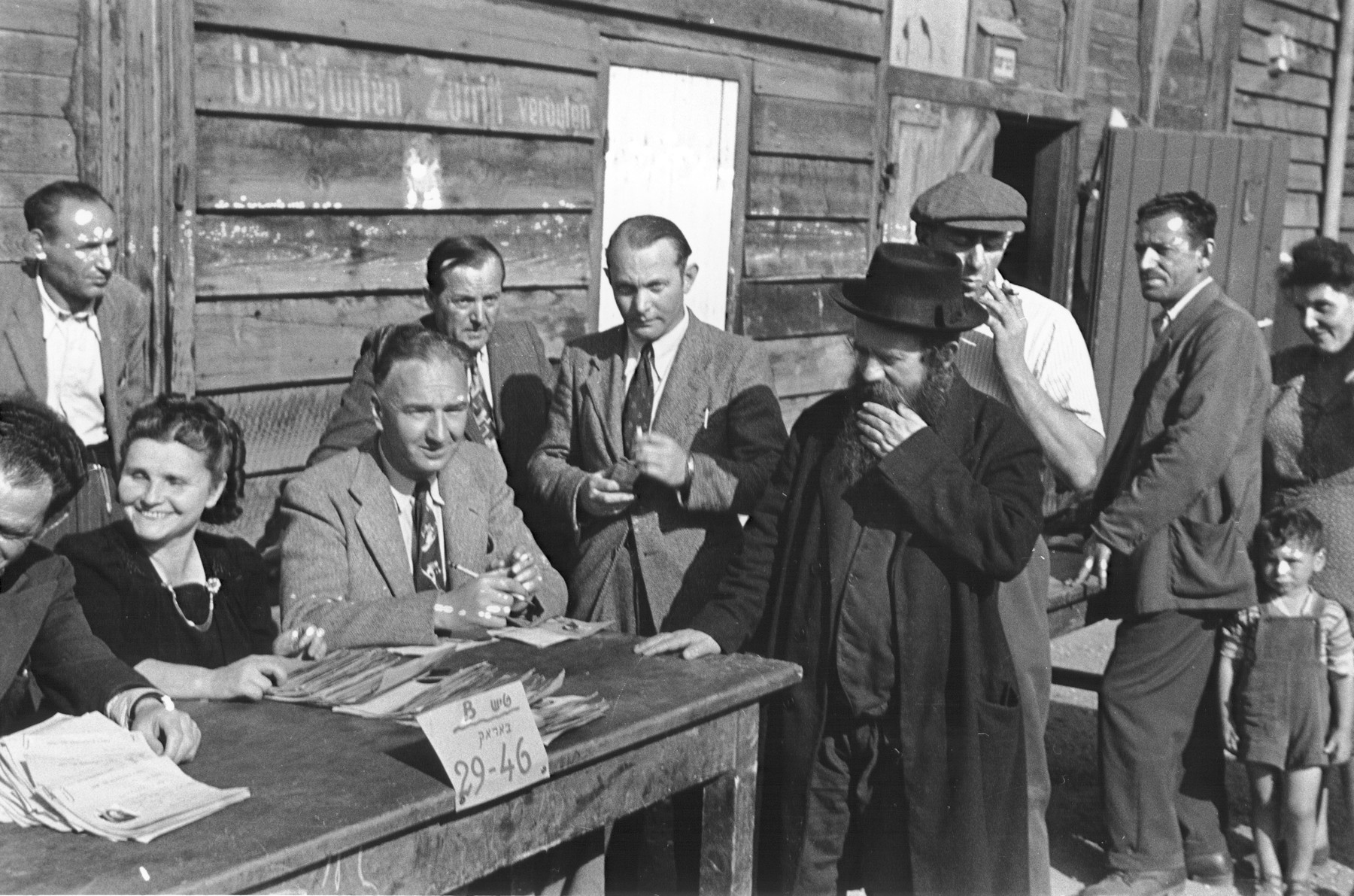 "Jewish DPs line up in front of a wooden barracks to register with IRO (International Relief Organization) officials.    The Hebrew sign on the table reads, ""Table B, Barracks 29-46."""