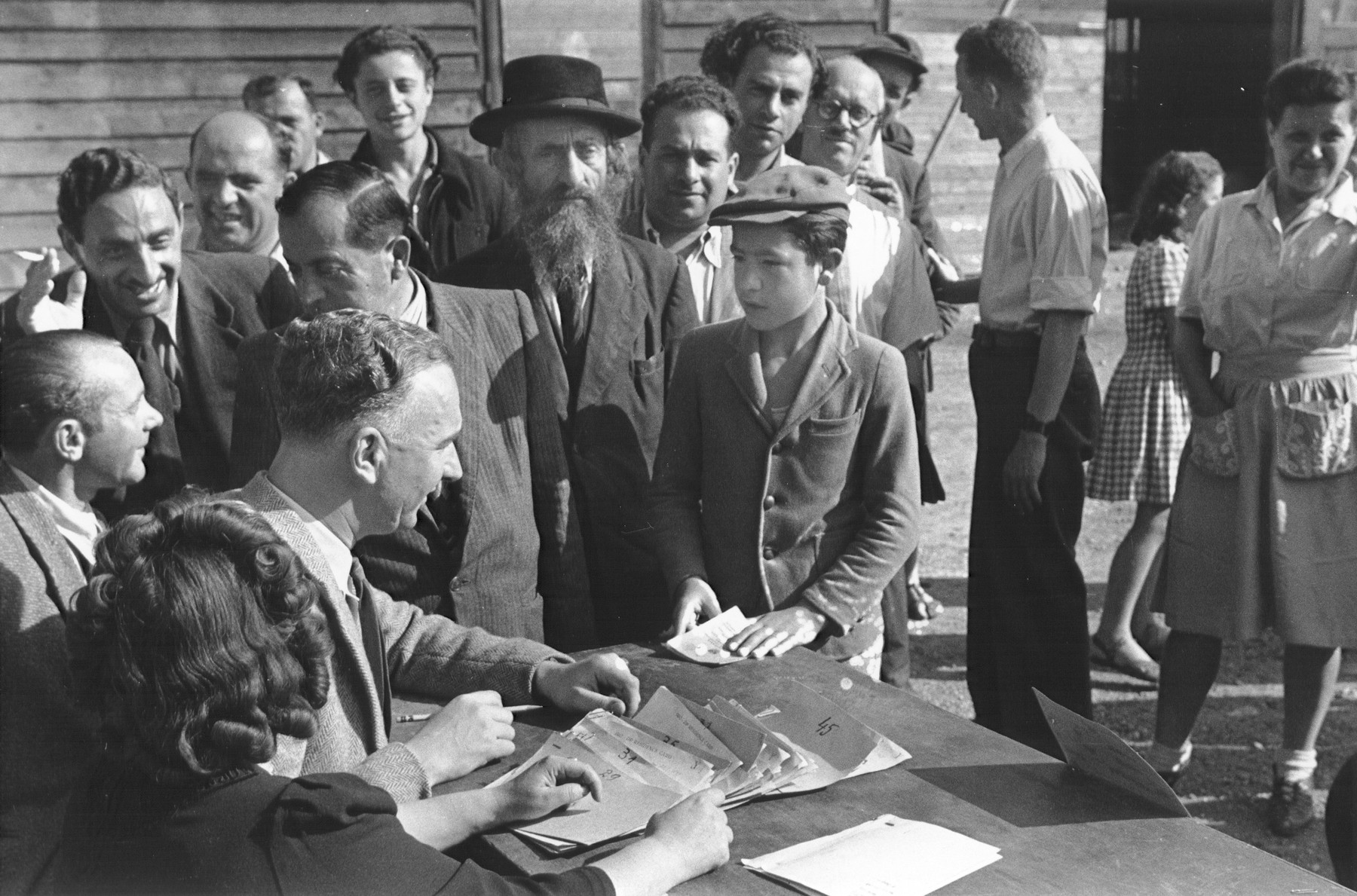 A Jewish DP child holding his identification card converses with an IRO (International Refugee Organization) official, who is seated at a table with a stack of IRO DP residence cards.