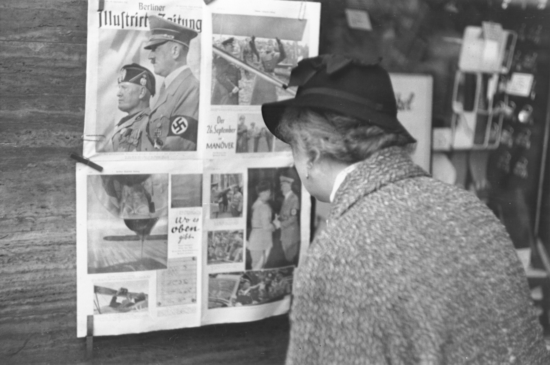 A German woman reads a copy of the Berliner Illustrierte newspaper that has been posted on a wall in Berlin.  It features photographs of Mussolini's official visit to Berlin in September 1937.