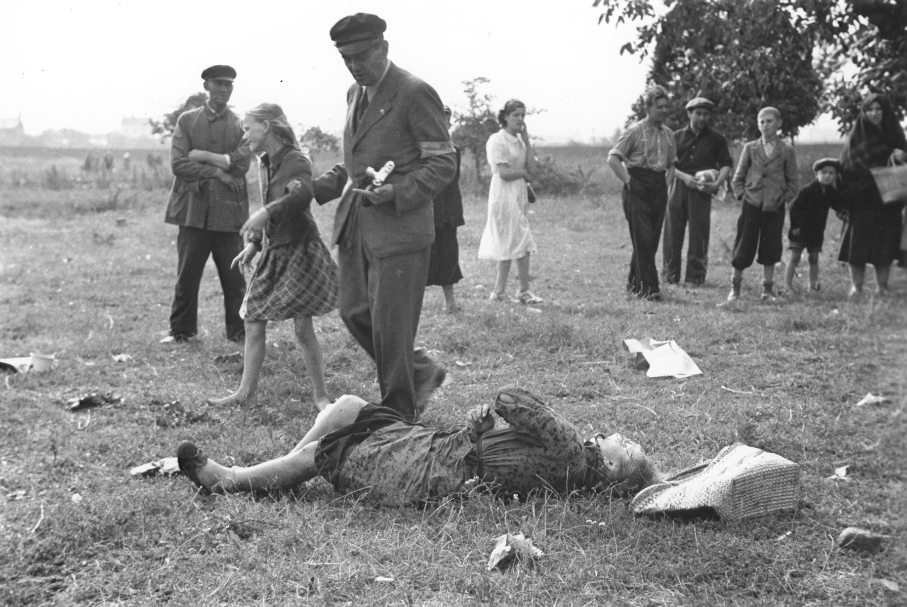 "A Polish man wearing an armband and holding a camera leads away a ten-year-old girl named Kazimiera Mika from the body of her older sister, who was killed in a field in Warsaw during a German air raid.  In the words of photographer Julien Bryan, ""As we drove by a small field at the edge of town we were just a few minutes too late to witness a tragic event, the most incredible of all.  Seven women had been digging potatoes in a field.  There was no flour in their district, and they were desperate for food.  Suddenly two German planes appeared from nowhere and dropped two bombs only two hundred yards away on a small home.  Two women in the house were killed.  The potato diggers dropped flat upon the ground, hoping to be unnoticed.  After the bombers had gone, the women returned to their work.  They had to have food.  But the Nazi fliers were not satisfied with their work.  In a few minutes they came back and swooped down to within two hundred feet of the ground, this time raking the field with machine-gun fire.  Two of the seven women were killed.  The other five escaped somehow.  While I was photographing the bodies, a little ten-year old girl came running up and stood transfixed by one of the dead.  The woman was her older sister.  The child had never before seen death and couldn't understand why her sister would not speak to her...  The child looked at us in bewilderment.  I threw my arm about her and held her tightly, trying to comfort her.  She cried.  So did I and the two Polish officers who were with me...""  [Source: Bryan, Julien. ""Warsaw: 1939 Siege; 1959 Warsaw Revisited."" Warsaw, Polonia, 1959, pp.20-21.]"