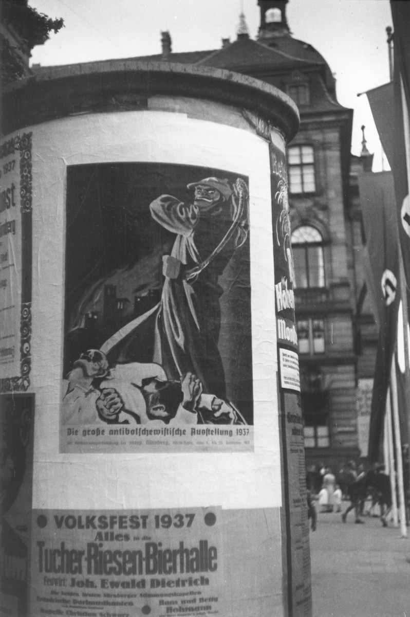 A poster advertising the Great Anti-Bolshevism Exhibition 1937 (Grosse Antibolschewistiche Ausstellung) is plastered on a kiosk on a city street in Nuremberg.