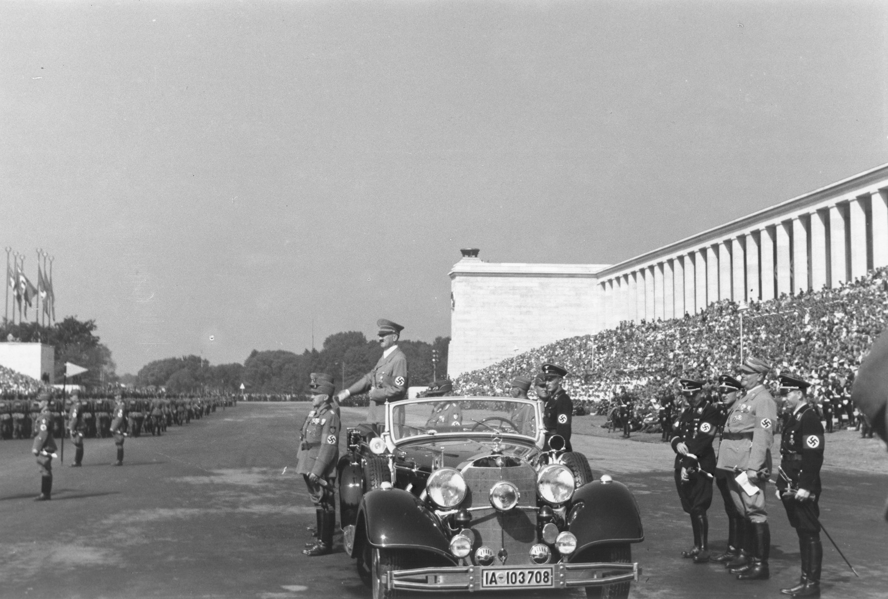 Adolf Hitler, standing in his open car, views the Reichsparteitag (Reich Party Day) gathering on the Zeppelin field in Nuremberg.