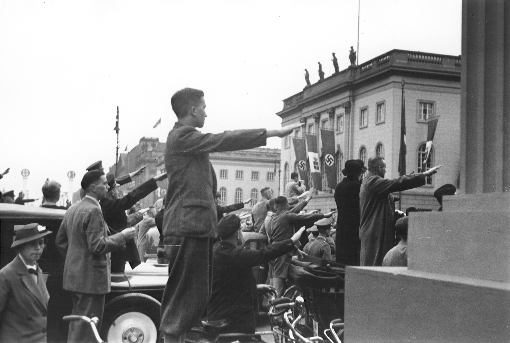 German spectators at a political rally raise their arms in the Nazi salute in Berlin.