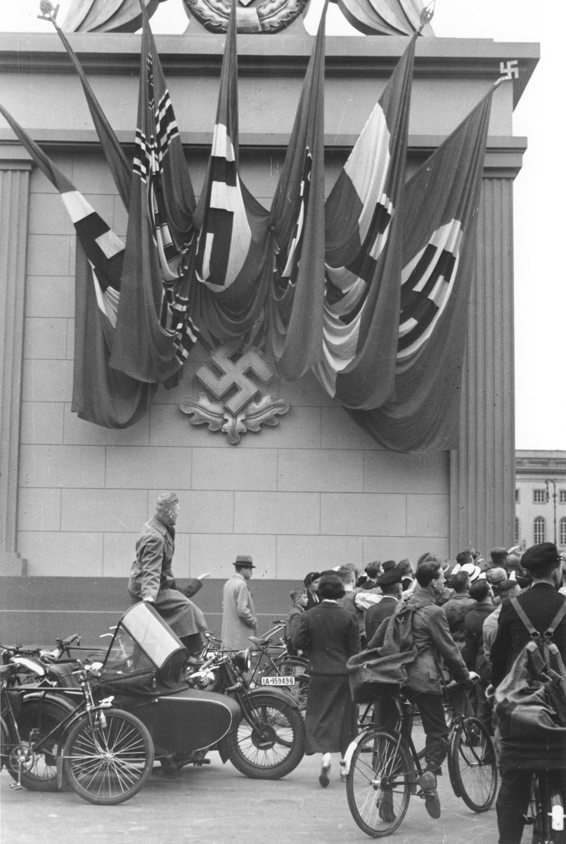 German spectators at a Nazi rally stand alongside a monument decorated with Nazi flags and a swastika emblem in Berlin.