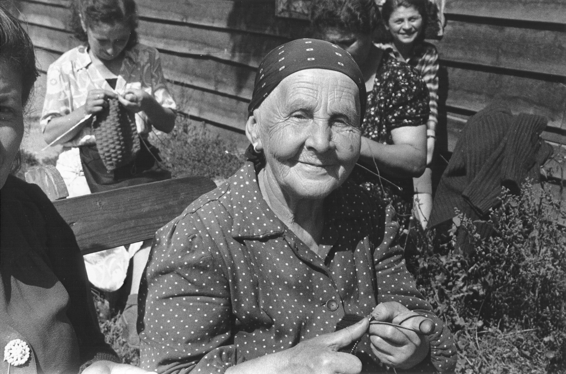 """Portrait of an elderly, Jewish DP woman, who is knitting outside with a group of women at a displaced persons camp in Austria.    Julien Bryan described this woman as follows: """"She was a grandmother in her eighties, living in an Austrian DP camp right after the war.  She was alone -- almost all of her relatives had been killed in the gas chambers of Auschwitz.  She was too old to be emigrated.  Her past destroyed, her future without hope, she seemed to possess an inner calm that allowed no place for bitterness.  I shall always remember her because she could still smile."""" [Source: International Film Foundation Catalog ca 1956]."""