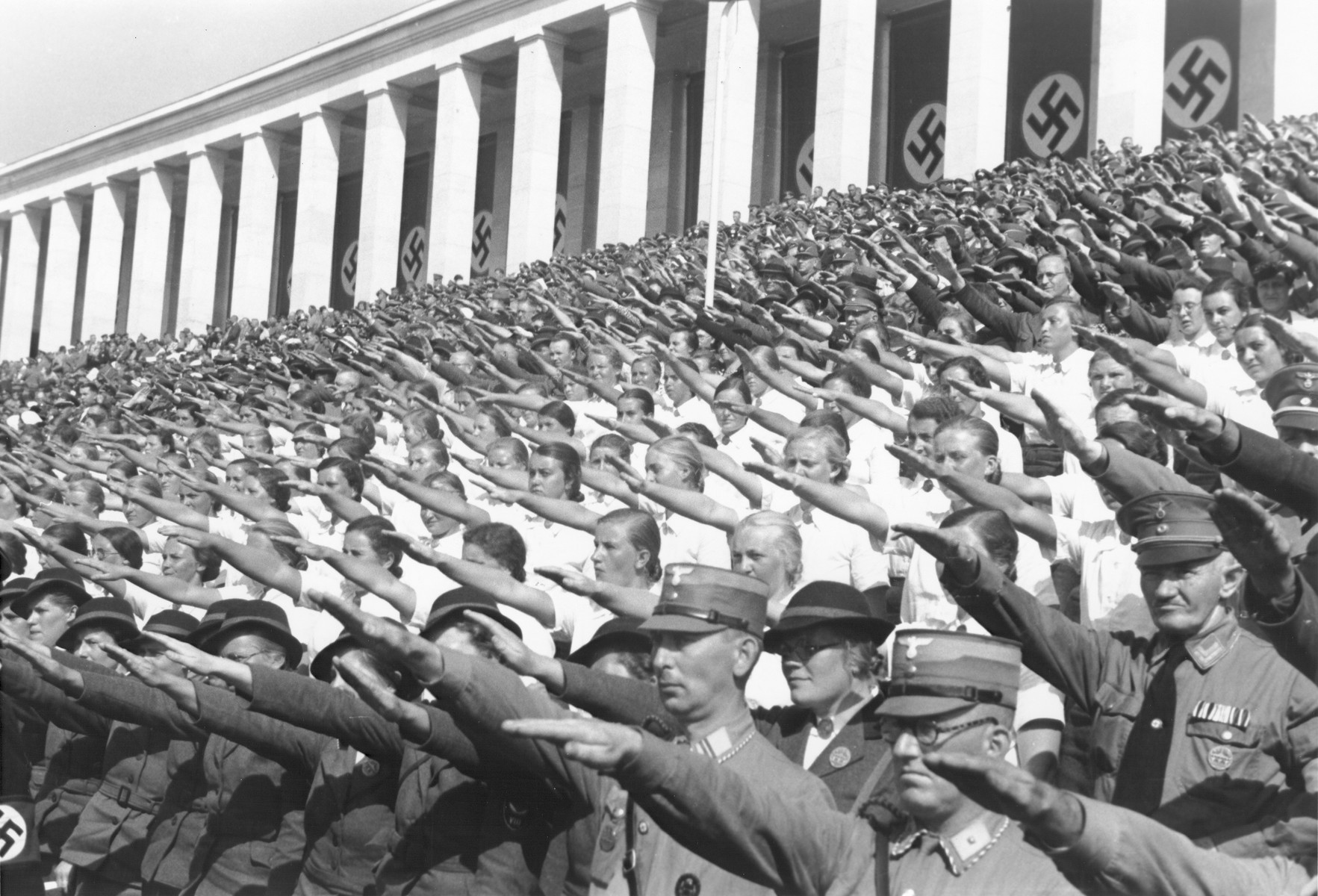 German spectators at the 1937 Reichsparteitag (Reich Party Day) celebrations in Nuremberg raise their arms in the Nazi salute.