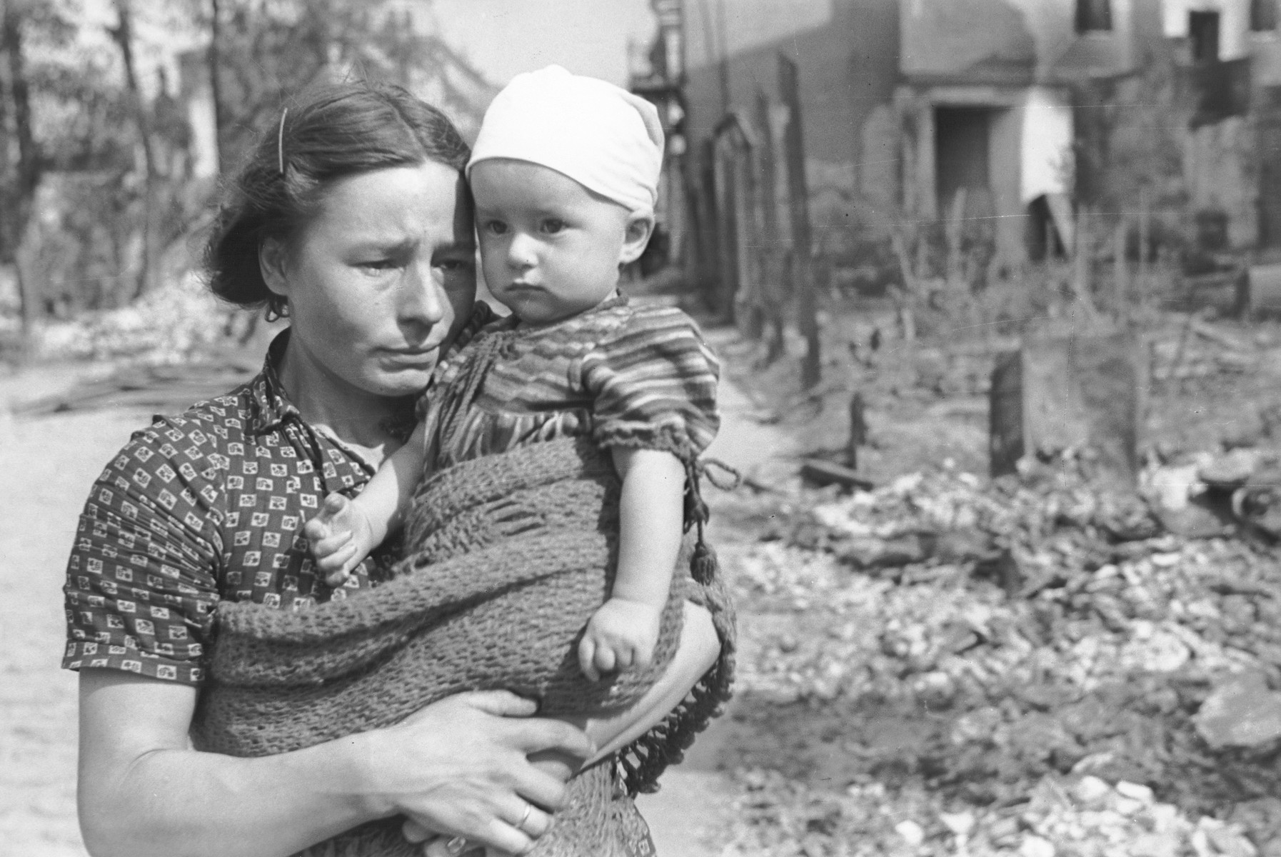A Polish mother and child pose amidst the rubble on a street in Warsaw that had been bombed during the siege of the capital.