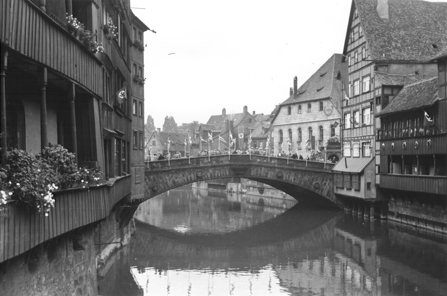 View of a bridge spanning a canal in Nuremberg.  The houses and bridge are bedecked with Nazi flags and banners.