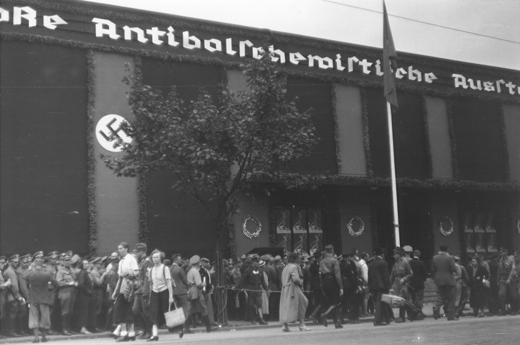Visitors line up in front of a hall adorned with Nazi banners in order to attend the opening of the Great Anti-Bolshevism Exhibition 1937 (Grosse Antibolschewistische Ausstellung) in Nuremberg.