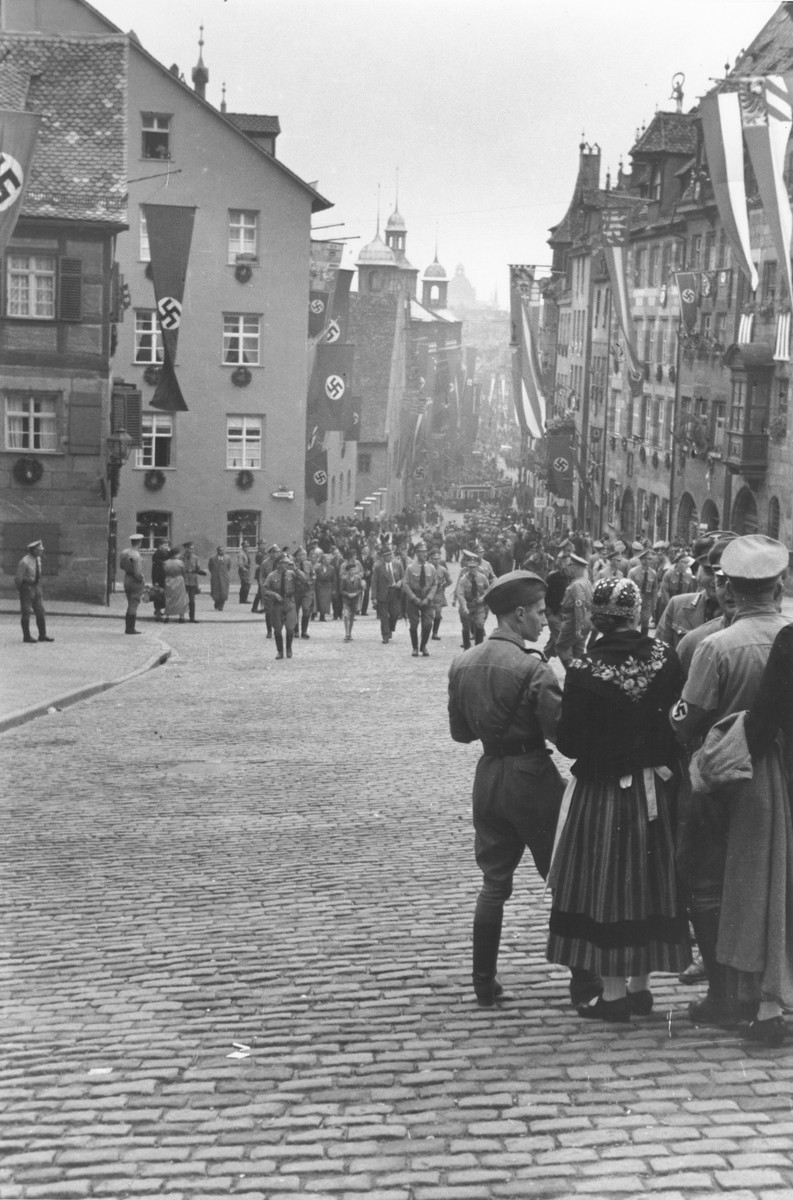 Uniformed Nazis congregate along a street in Nuremberg that is bedecked with Nazi banners [probably in celebration of the Reichsparteitag (Reich Party Day) of 1937].