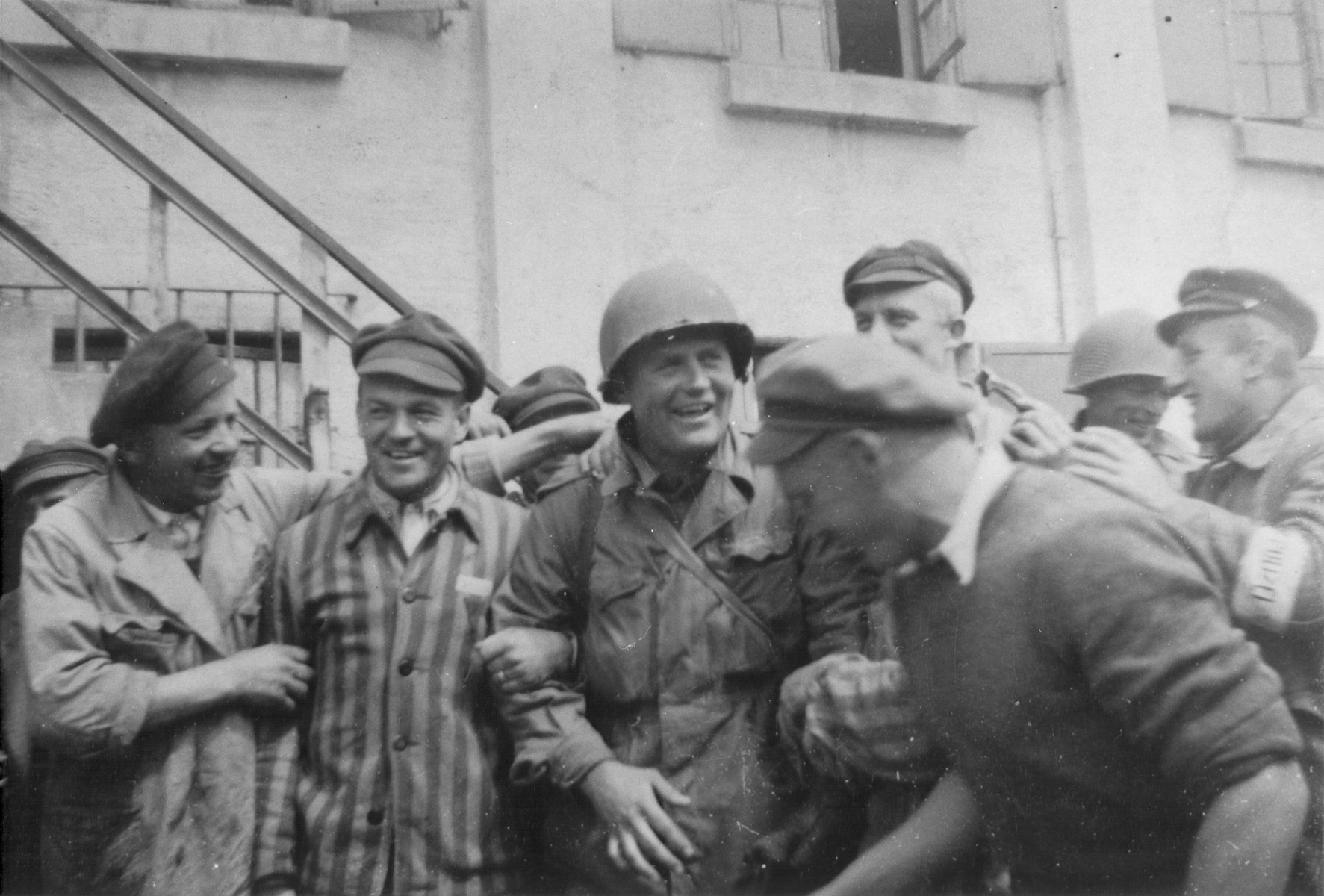 An American officer is surrounded by survivors at the newly liberated Dachau concentration camp.