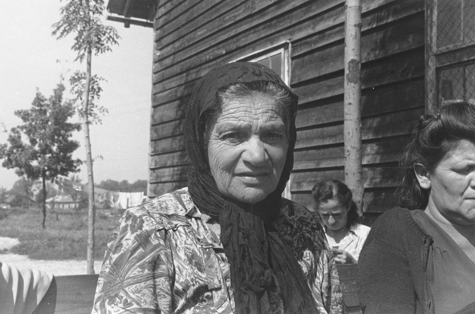 Portrait of an elderly, Jewish DP woman, who is seated outside on a bench among other women who are knitting, at a displaced persons camp in Austria.