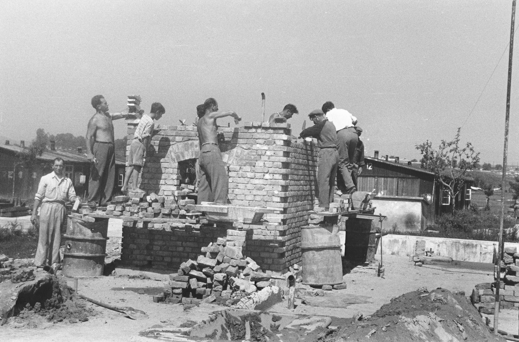Under the guidance of an ORT instructor, Jewish DPs learn bricklaying by constructing a small brick building at a Jewish displaced persons camp in Linz.