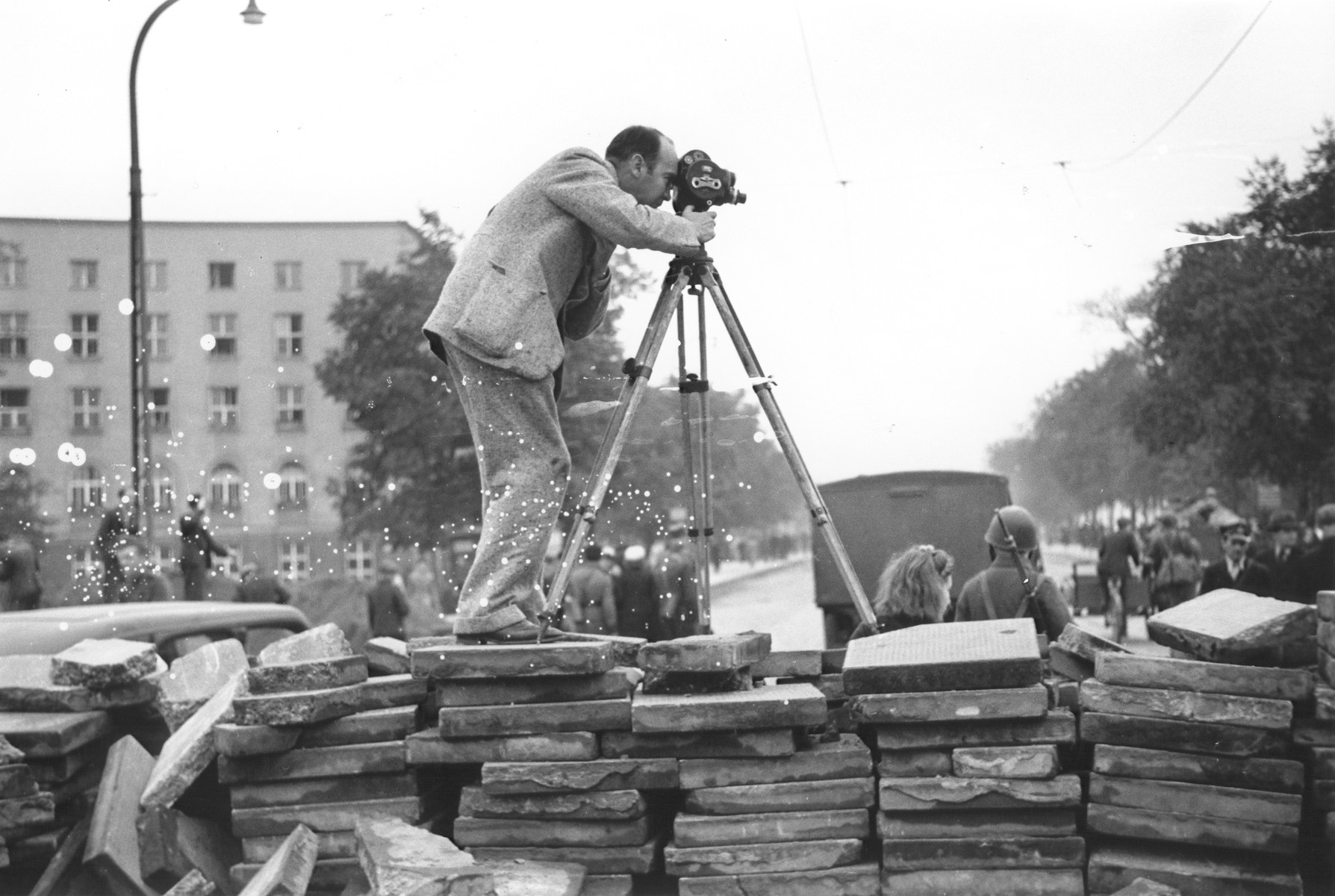 American photographer Julien Bryan films a scene duing the siege of Warsaw.  He stands atop a barricade of paving stones that had been erected to slow the advance of the German army.