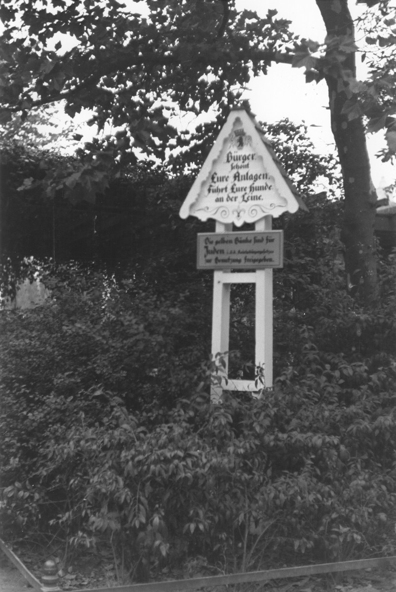 """A decorative sign in a public park in the Olivaerplatz reads: """"Citizens protect your public spaces.  Keep your dogs on a leash.  The yellow benches are for Jews (in accordance with the Reich's law) for their free use."""""""