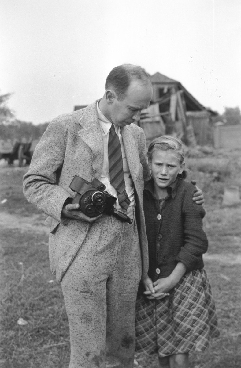 """Photographer Julien Bryan comforts a ten-year-old Polish girl named Kazimiera Mika, whose older sister was killed in a field in Warsaw during a German air raid.  In the words of photographer Julien Bryan, """"As we drove by a small field at the edge of town we were just a few minutes too late to witness a tragic event, the most incredible of all.  Seven women had been digging potatoes in a field.  There was no flour in their district, and they were desperate for food.  Suddenly two German planes appeared from nowhere and dropped two bombs only two hundred yards away on a small home.  Two women in the house were killed.  The potato diggers dropped flat upon the ground, hoping to be unnoticed.  After the bombers had gone, the women returned to their work.  They had to have food.  But the Nazi fliers were not satisfied with their work.  In a few minutes they came back and swooped down to within two hundred feet of the ground, this time raking the field with machine-gun fire.  Two of the seven women were killed.  The other five escaped somehow.  While I was photographing the bodies, a little ten-year old girl came running up and stood transfixed by one of the dead.  The woman was her older sister.  The child had never before seen death and couldn't understand why her sister would not speak to her...  The child looked at us in bewilderment.  I threw my arm about her and held her tightly, trying to comfort her.  She cried.  So did I and the two Polish officers who were with me...""""  [Source: Bryan, Julien. """"Warsaw: 1939 Siege; 1959 Warsaw Revisited."""" Warsaw, Polonia, 1959, pp.20-21.]"""