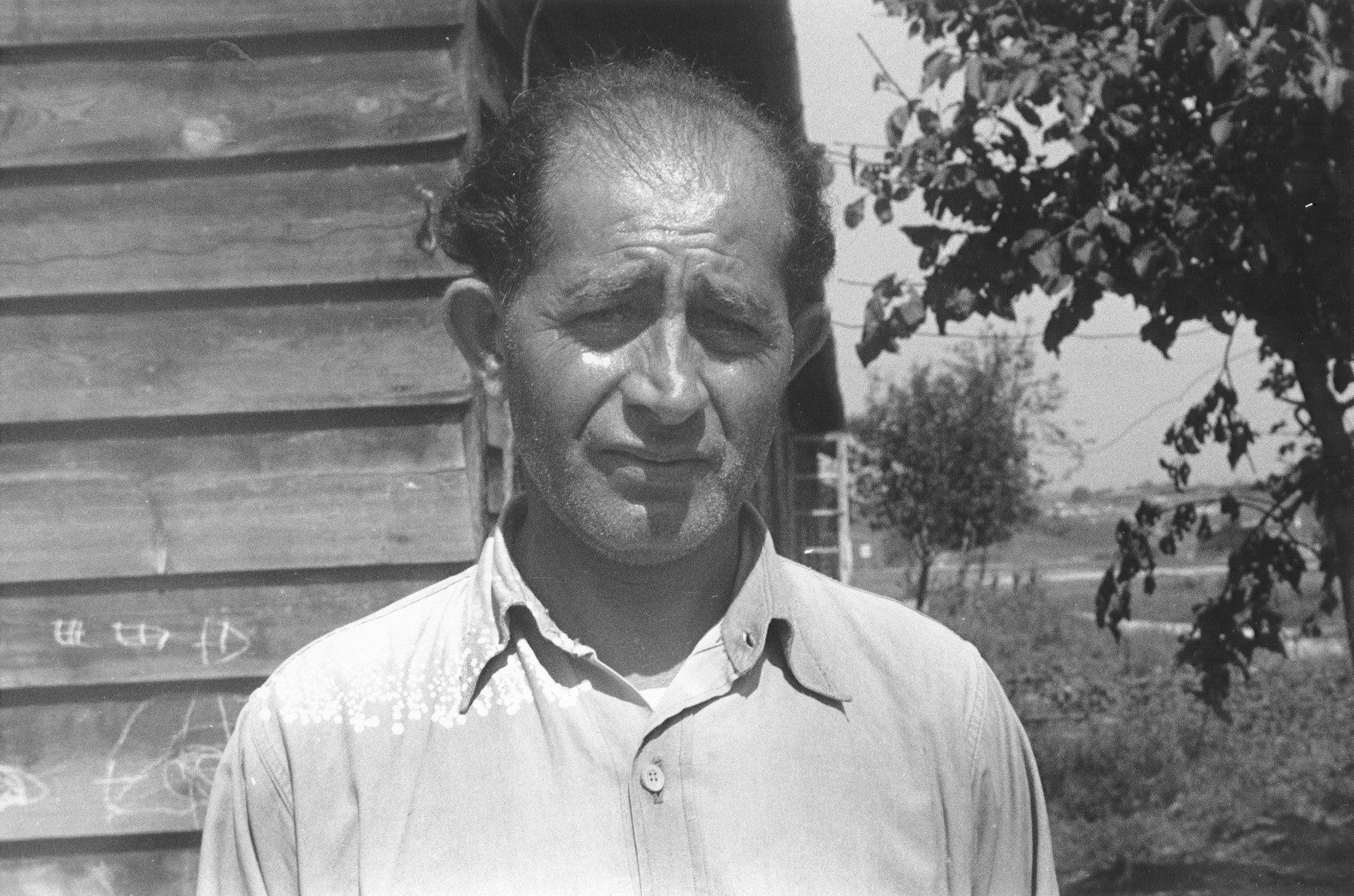 Portrait of a Jewish DP standing in front of a wooden barracks in a displaced persons camp in Austria.