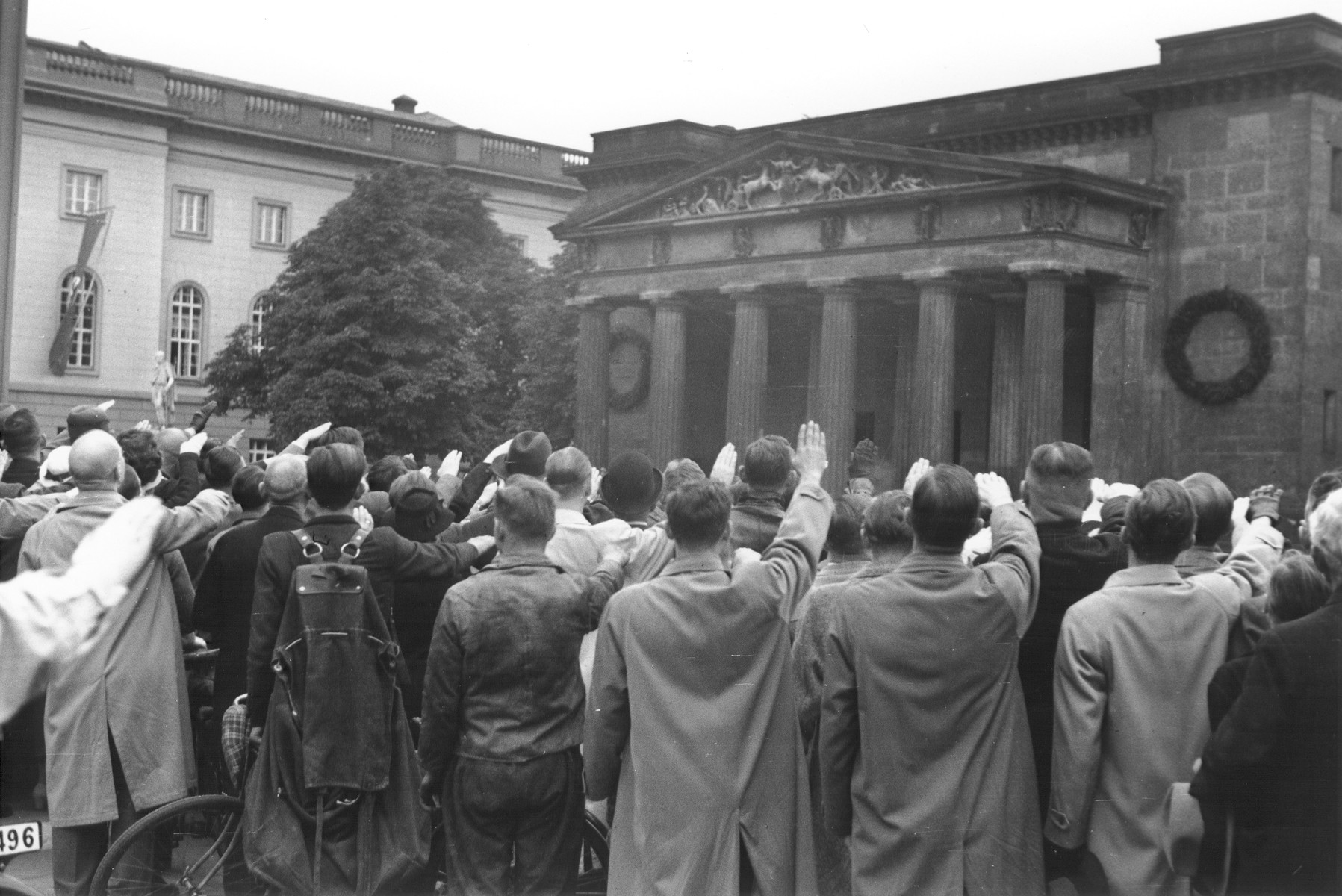 German spectators at a political rally in front of a war memorial raise their arms in the Nazi salute.
