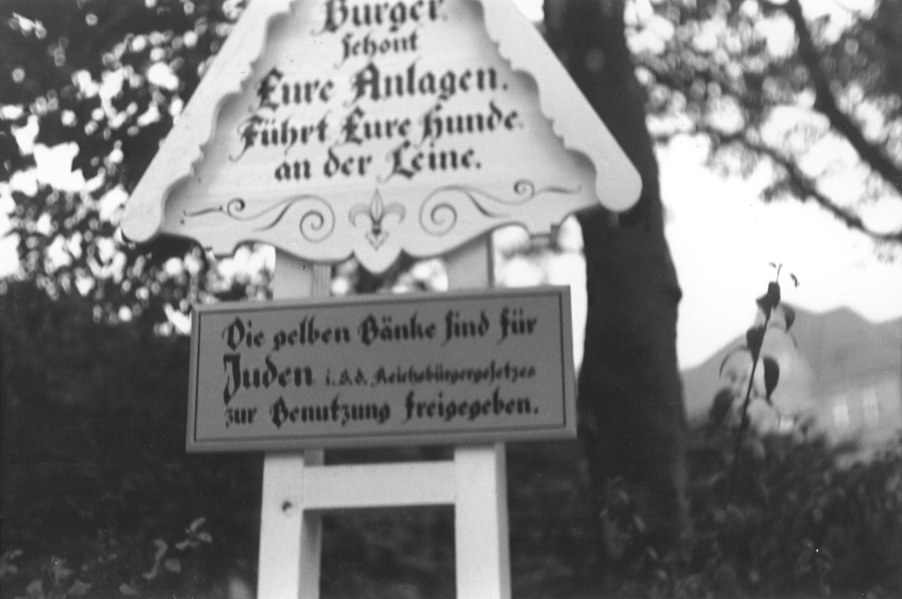 """A decorative sign in a public park in the Oliviaplatz reads: """"Citizens protect your public spaces.  Keep your dogs on a leash.  The yellow benches are for Jews (in accordance with the Reich's law) for their free use."""""""