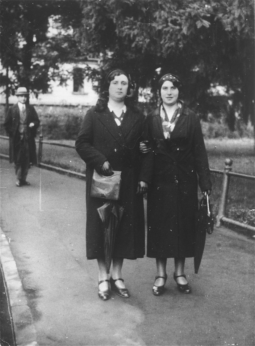 Frymet Kramarski (mother of the donor) walks down the street with her sister Szaidal Borenstein.  Both women perished in the Holocaust.