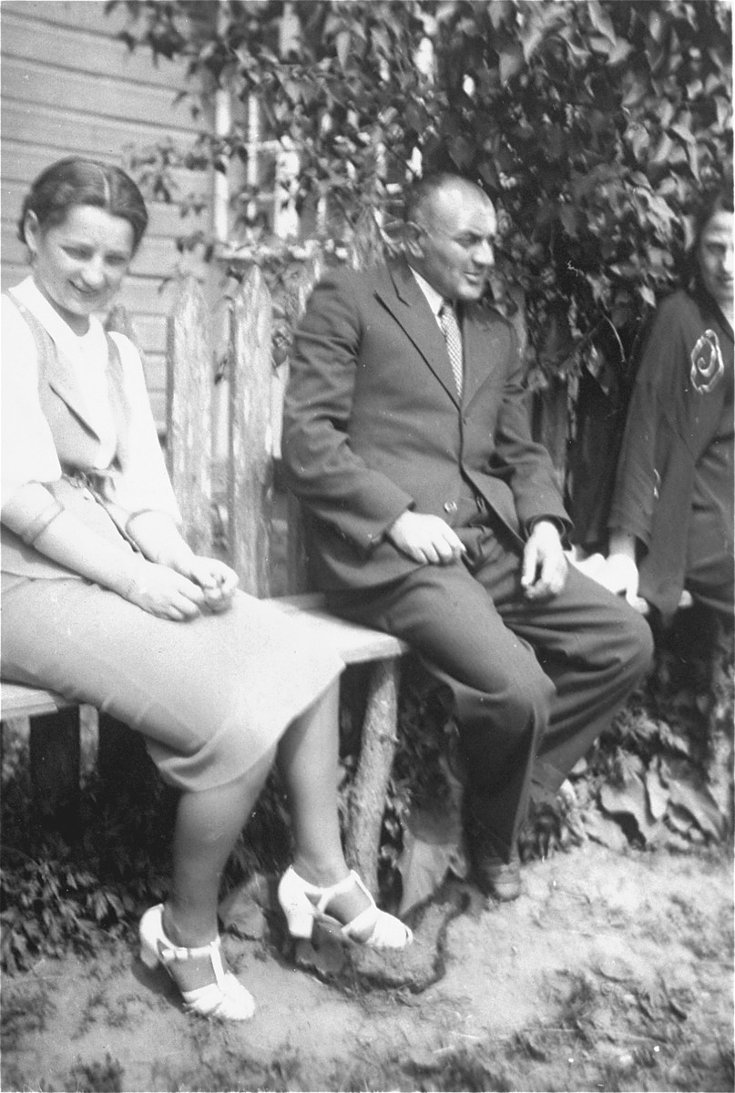 A Jewish man and woman from Sejny sit outside a wooden house.  The man is Peretz (exact name unknown); the brother-in-law of Zelig Szczupacki.  Peretz owned an iron-goods store.  His father in-law Avram was a blacksmith.