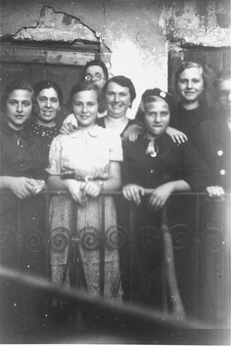 Members of the Petranker and Hut families pose on a balcony.  Pictured from left to right are: Amalie Petranker, Klara Hut, Celia Petranker, David Petranker (behind), Frieda Petranker, Paulina Hut, Pepka Petranker, and Jakub Hut.