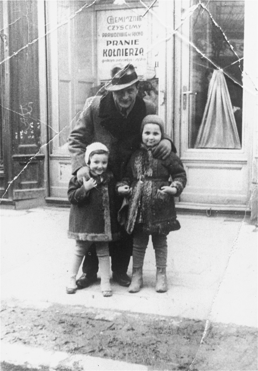 A Jewish man poses with his two nieces on a street in Rzeszow, Poland.  Pictured are David Greenspan with his nieces, Marta Wistrich and Greta Heller.
