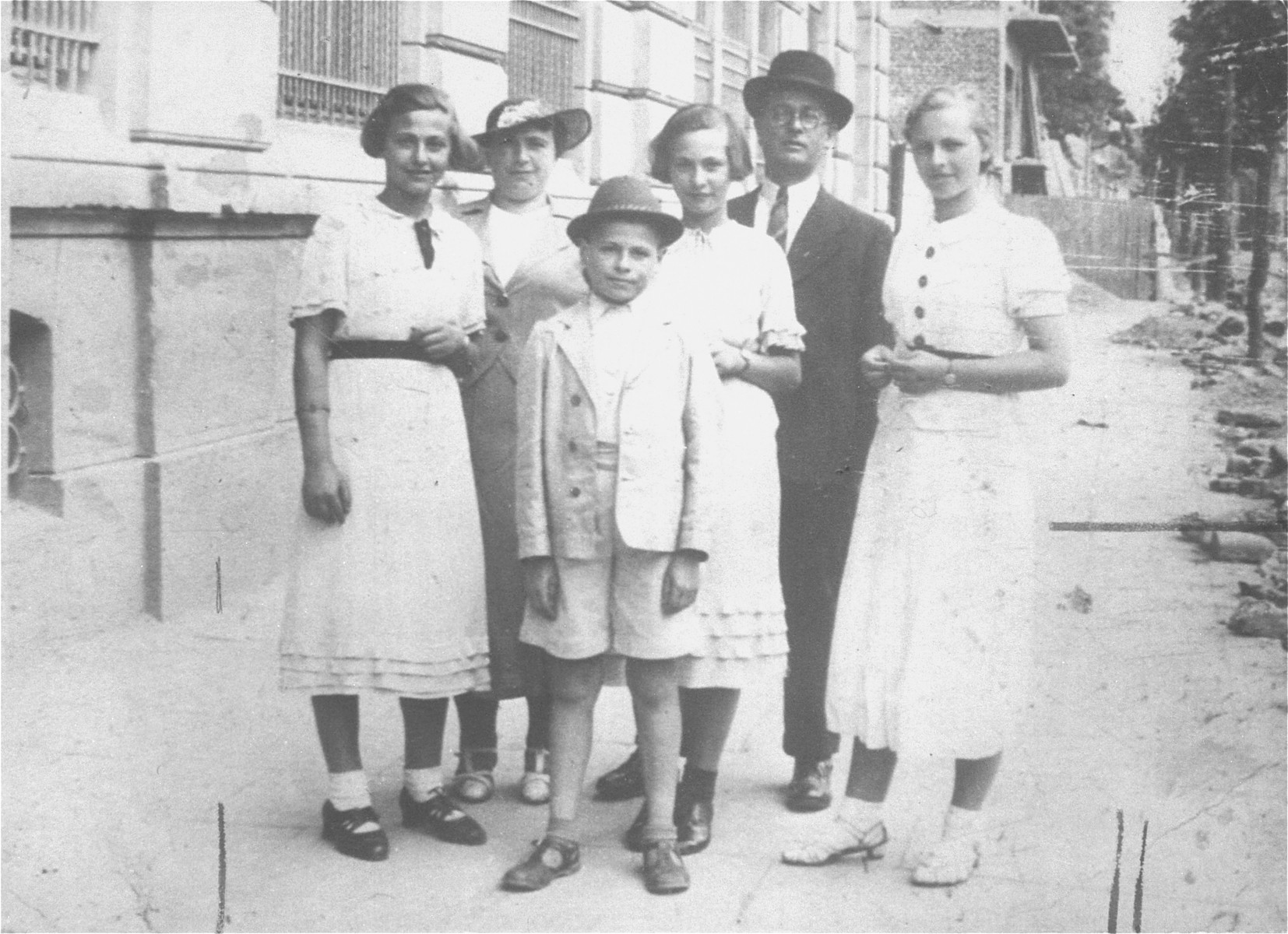 Members of the Petranker family pose on the street in Stanislawow.  Pictured from left to right are: Amalie Petranker; Frieda Petranker (behind); Menashe Honigsberg; Celia Petranker; David Petranker, and Pepka Petranker.   Menashe was a cousin who came to live with the Petrankers after the death of his mother.