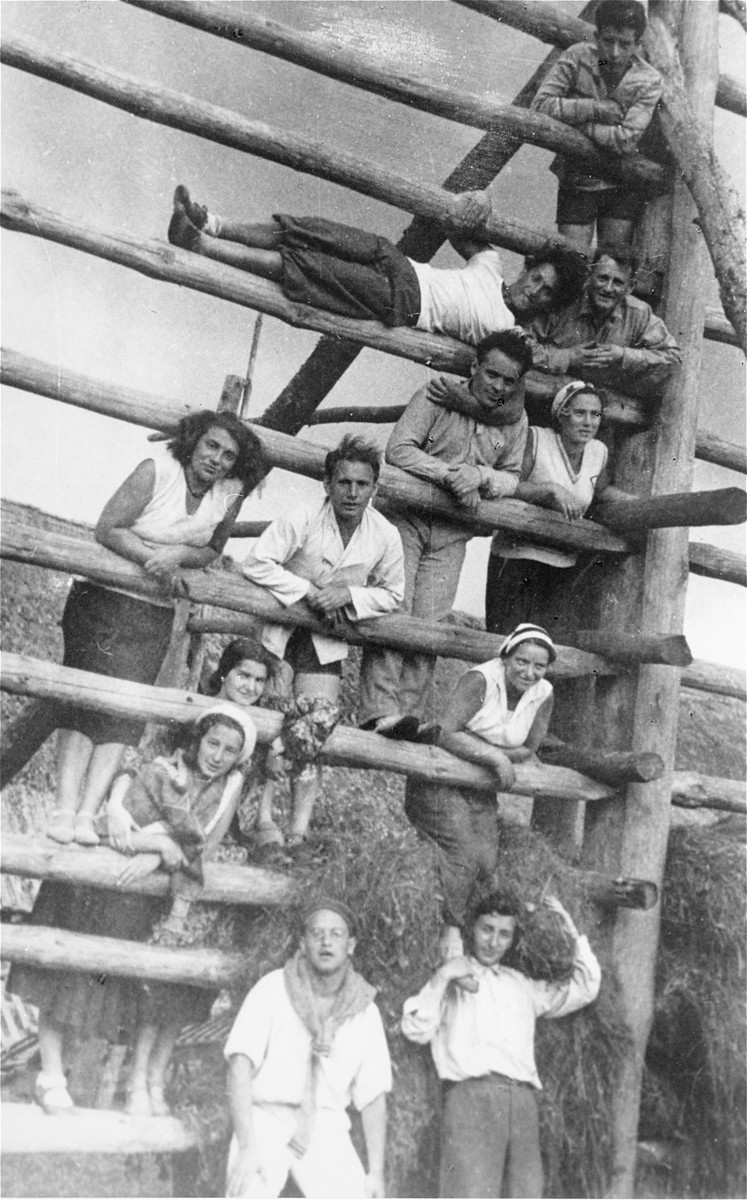 Members of the Jewish Socialist Bund pose on the rungs of a high fence while on an outing.   Among those pictured is Avraham Jurer (bottom, left).