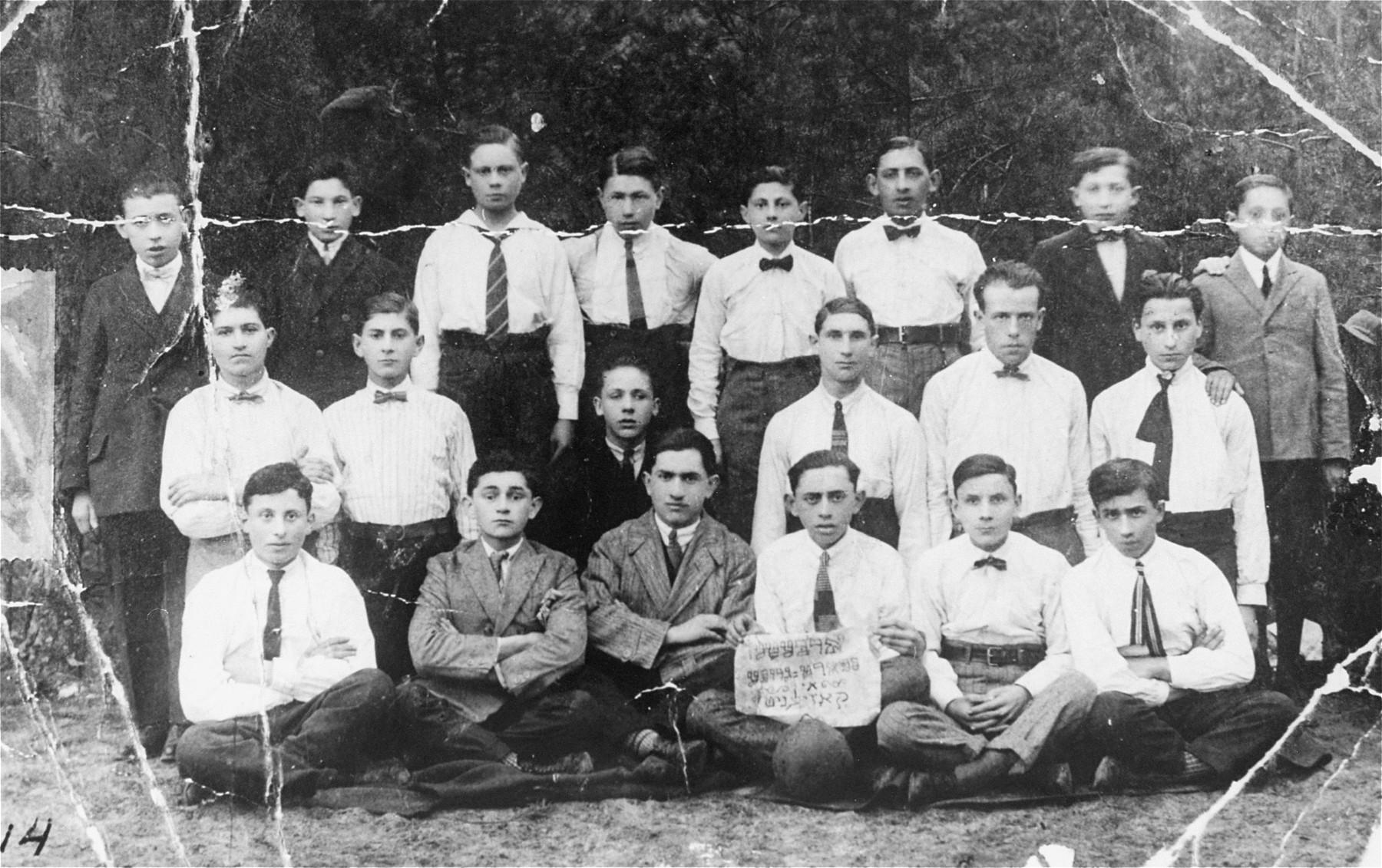 "Group portrait of members of the Bund socialist youth movement in Kozienice.  The Yiddish sign reads: ""Workers' sports group in Kozienice.""  Among those pictured are: Shlomo Huberman, Matl Steinboim, Israel Herman, Moshe Kahan, Shalom Blaunis, Daniel Weinberg, Yankel Weinberg, Gedalia Weinberg, Michael Rogal, Ezra Arbeitman, Chaim Hartman, Leibush Zaterman and Binem Provisor."