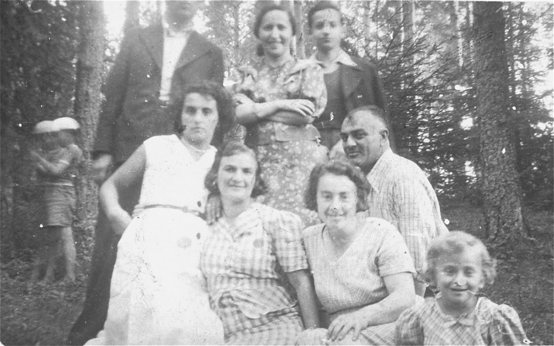 Friends and relatives of a Jewish family from Sejny pose for a group portrait in the woods.  Pictured are relatives of the Szczupacki family.