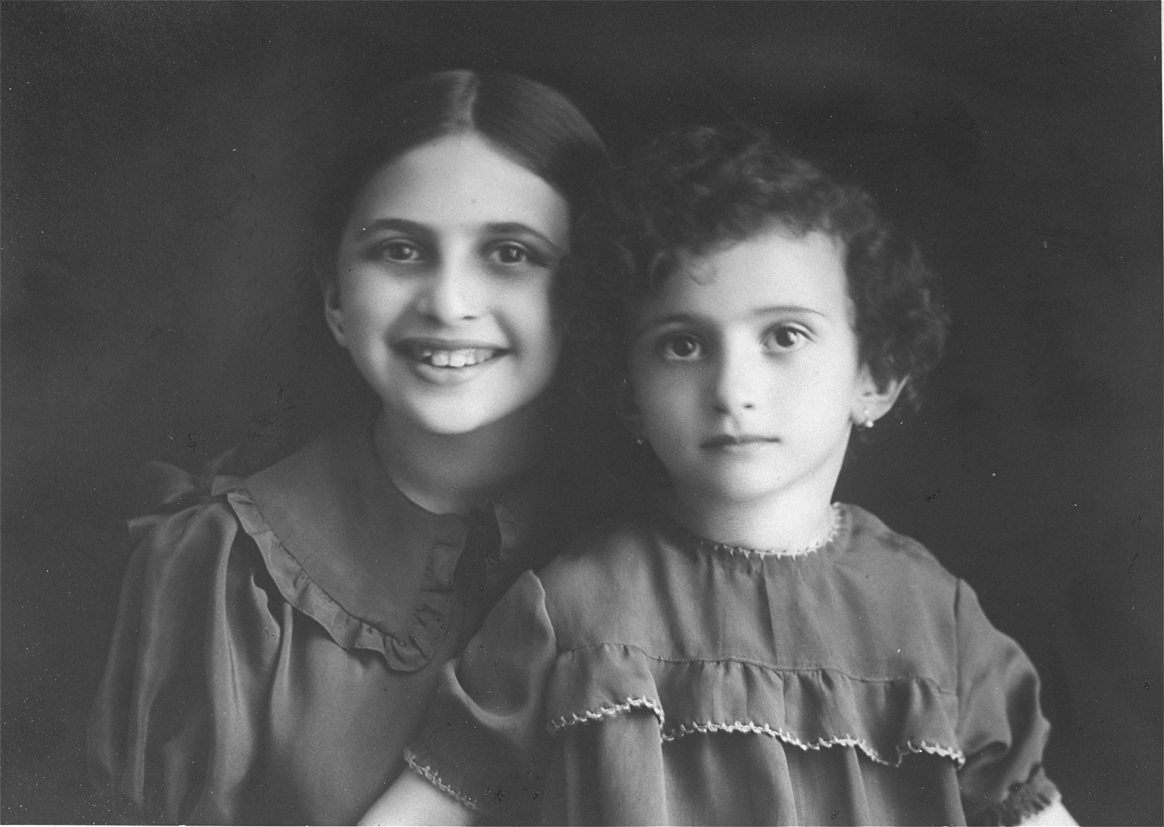 """Portrait of Fella and Rita Pressner, at ages 8 and 4.  Morris and Sala Pressner lived in Zaleszczyki, on the Romanian border, with their two daughters, Fella, the donor and Rita.  In 1934 the family left Poland for Paris, France, where the father, Morris and his brother, Jules, represented the Pressner family business.  In June 1940 the family escaped from Paris to Marseilles.  Thanks to the help of the Pressner family in America a Cuban entry visa was secured in October 1941.  The family that consisted of 9 members left for Havana, Cuba from Lisbon on the Portuguese ship """" Serpa Pinto"""".  In April 1944 Fella and her family emigrated to the U.S."""