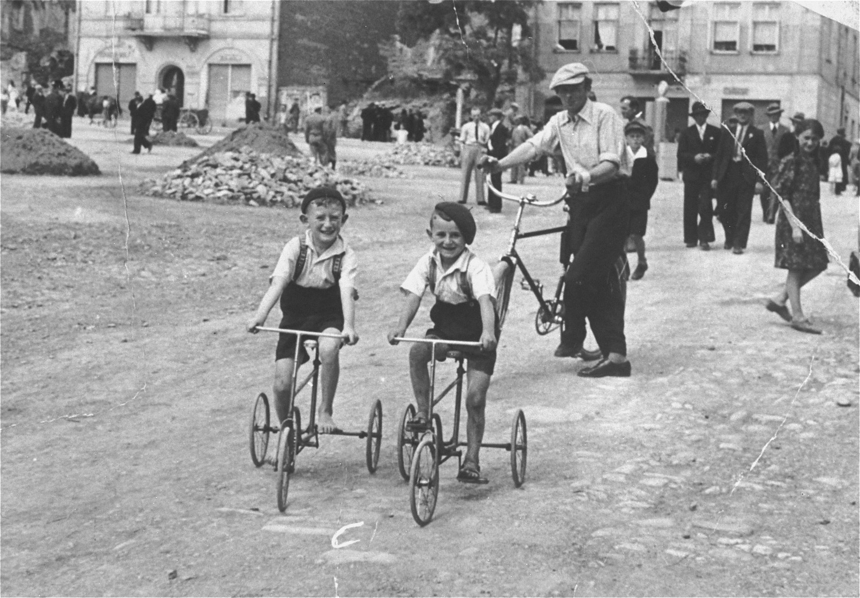 Two Jewish children ride tricycles along a street in Rymanow, Poland.  Pictured are Abraham Keller Landau (behind with the bicycle) and his nephews Natan Chulef Keller and Jaime Chulef Keller.