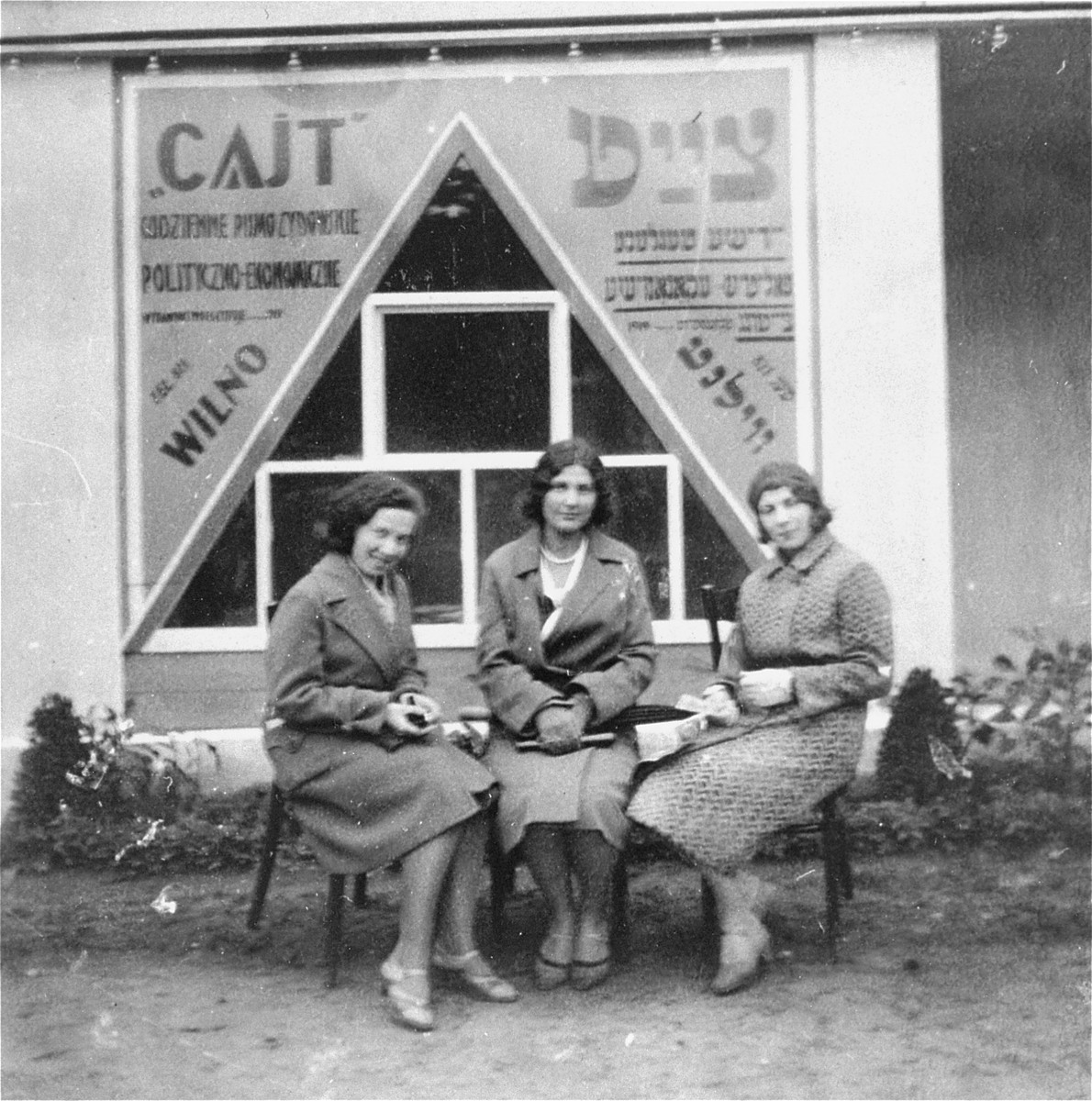 "Three young Jewish women sit in front of the editorial office of the Yiddish daily newspaper, ""Cajt"".  Pictured from right to left are: Raya Magid; her sister Katia Magid; and a friend, Nuta Klausner."