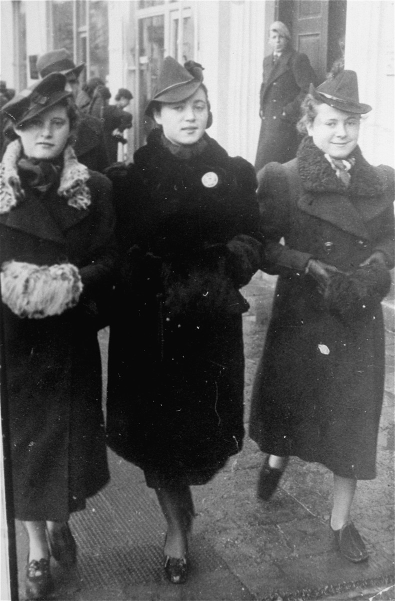 Three young Jewish women walk along a street in Radom.   Pictured are Guta, Lifcia and Ethel Najman (three sisters). Lifcia was the wife of the donor, Lewis Shabasson.