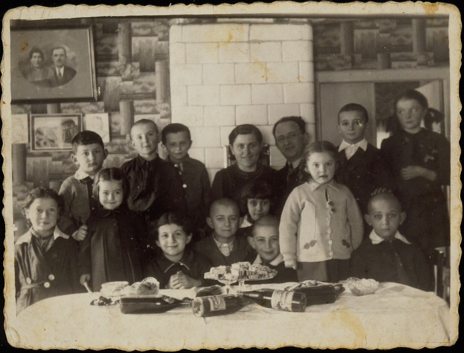 A joint birthday party for cousins Shula and Yaffa Sonenson in Eisiskes.    Pictured in the back row from right to left are: Hannkeh Tawlitski, Elisha Koppelman, Shalom and Miriam Sonenson (the hosts of the party), Shmuel Sonenson; Hayyim Tawlitski and Meir Sonenson.  In the front row from right to left are: Shaul Replianski, Yaffa and Yitzhak Sonenson, Sheinke Dwilanski, Benyamin, Gittele, Shula Sonenson and Leahke Tawlitski.  Hanging on the wall is a photograph of Miriam Sonenson's parents and a painting of Jerusalem flanked by marble reliefs of Theodor Herzl and Nahman Hayim Bialik.  Of those pictured only Shalom, Yitzhak and Yaffa Sonenson survived. Elisha Koppelman was killed by members of the Polish Home Army; Gittele died from tuberculosis in the Korkuc pit;  Miriam and Shula were killed by Germans during an action in the Radun ghetto.  The others were killed by the Germans during the September 1941 mass shooting action in Eisiskes.