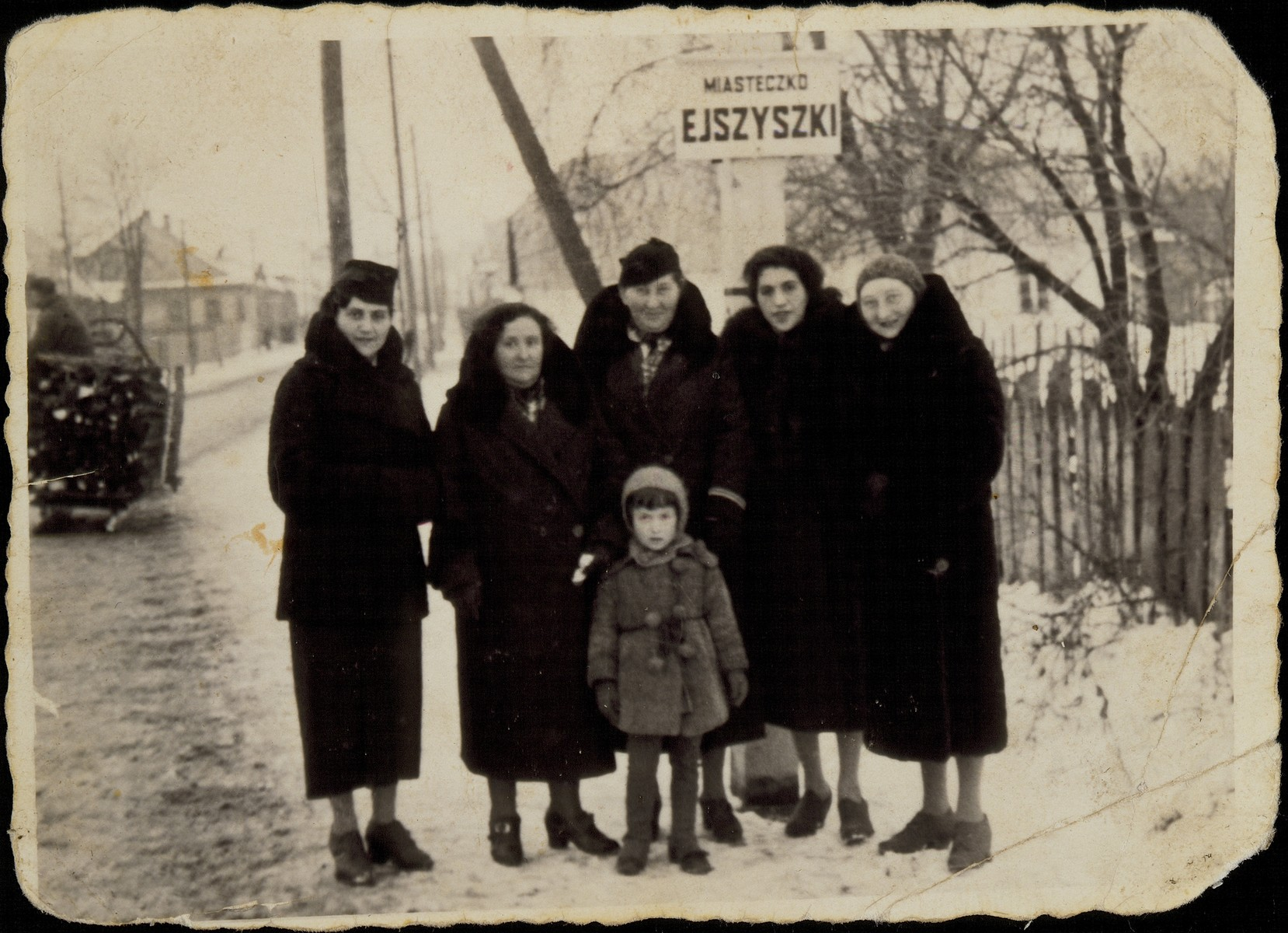 A group of Jewish women pose with a young girl at the entrance to Eisiskes.  Pictured from right to left are: Zipporah (Katz) Sonenson, Masha Michalowski, Alte Katz, Maite Gurewitch and Miriam Sonenson.  Standing in front of them is Shula Sonenson, the daughter of Miriam.  Of those pictured only Masha Michalowski survived the war and its aftermath.