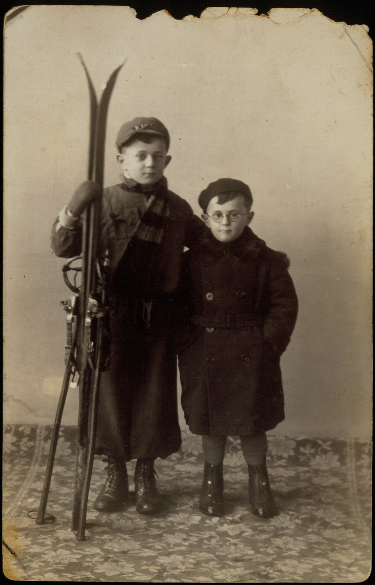 Studio portrait of two Jewish brothers, one holding a pair of skis.  Pictured are Benyamin (left) and Shmuel Sonenson in 1938. Both were killed by the Germans in the September 1941 mass shooting action in Eisiskes.