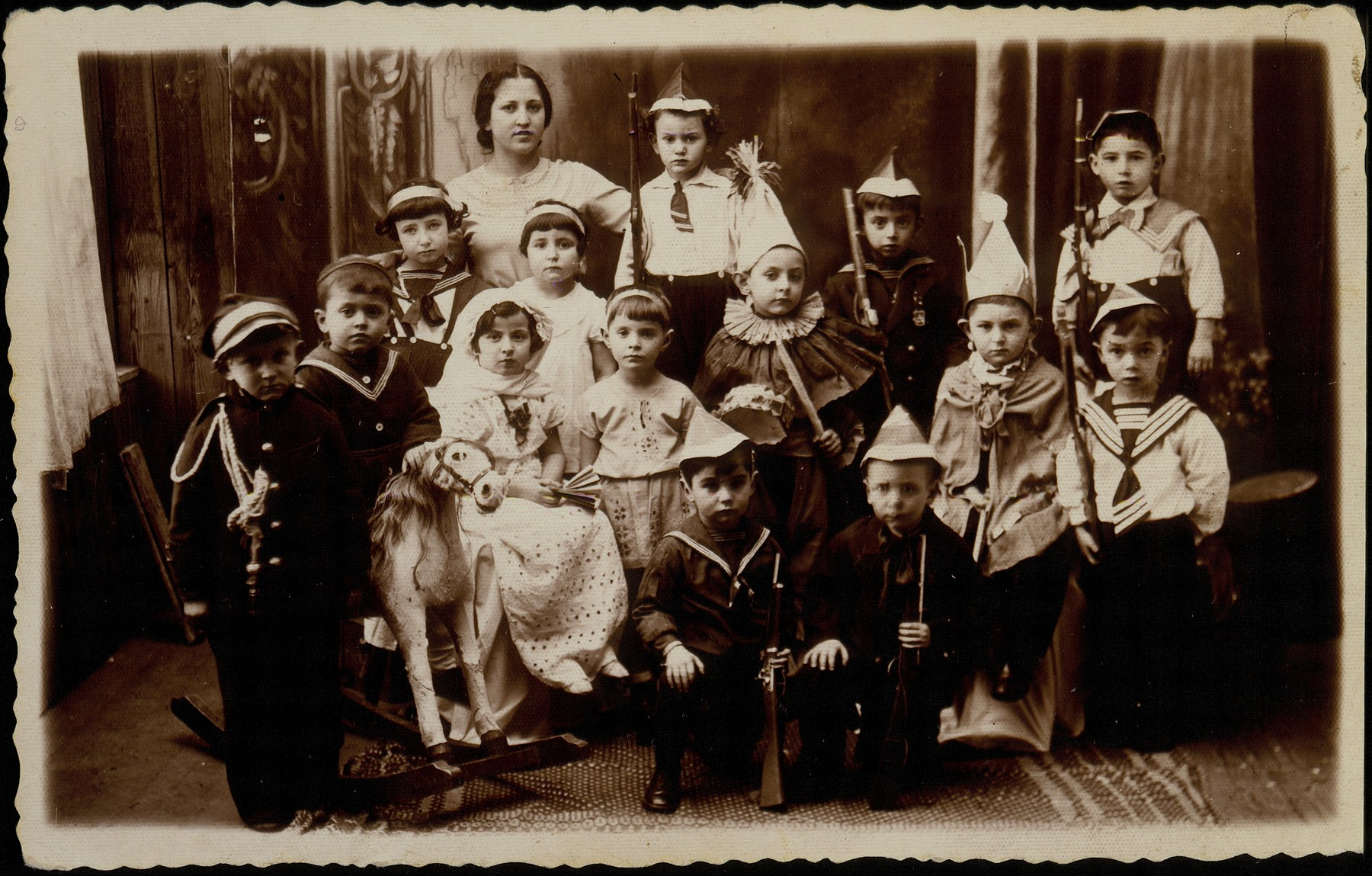 Group portrait of Jewish children from the Hebrew kindergarten in Eisiskes, dressed in costumes for a Purim play.  Pictured in the back row from right to left are: Yudaleh Kabacznik, unknown, Elisha Koppelman and Dora Feller;  in the third row from right to left are: Slepak, Yitzhak Sonenson, Yehudah Schneider, Hannah Shawitski and Reizele Erlich; in the second row from right to left are: Pola Berkowicz, Gittele Sonenson, Mordekhai Bichwid and Arieh Krisilov; sitting in front are: Yaakov Kaganov (right) and Hayyim Gershowitz (left).  Dora Feller immigrated to Palestine; Yaakov Kaganov was killed in a car accident in the United States; Gittele Sonenson died from tuberculosis while in hiding in a pit during the war.