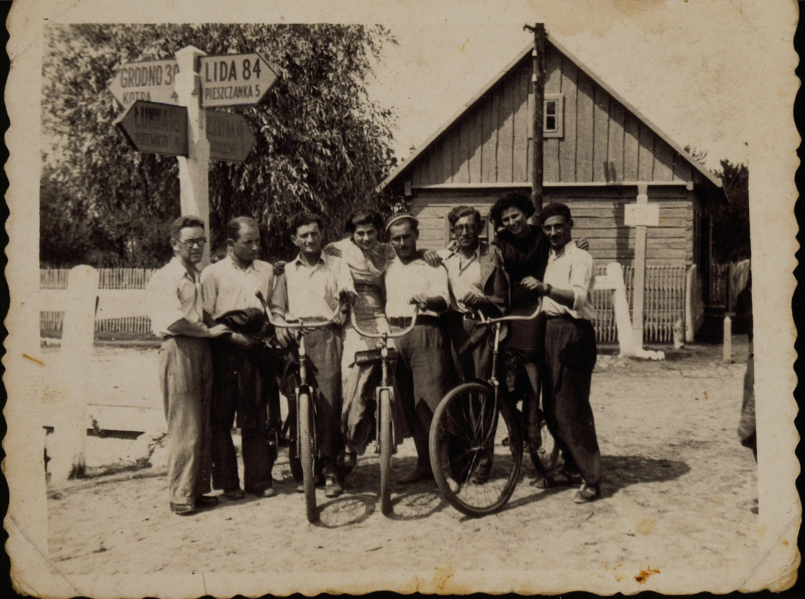 Winners of a bicycle race sponsored by local Zionist groups, pose with their bicycles next to a road sign in the village of Skidel.  Among those pictured is Shabbtai (Shepske) Sonenson (third from the left), who represented the Betar organization in Eisiskes.  Shepske was killed by the Germans during the September 1941 mass shooting action in Eisiskes.