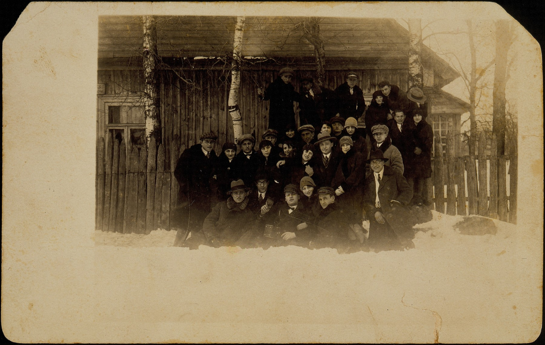 Several Jewish families who are celebrating the holiday of Hanukkah together, pose outside a wooden house in Eisiskes.  Pictured are members of the Sonenson, Kabacznik and Kaganowicz families with Shaul Dubrowicz.