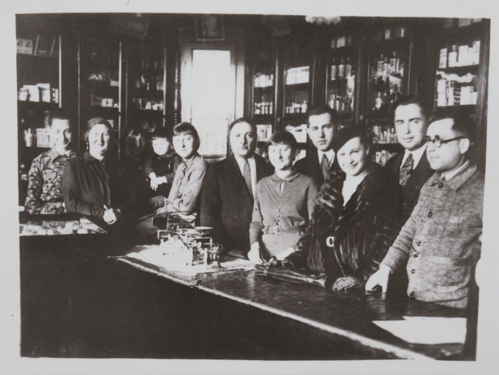 Staff and customers stand in front of the counter in the Katz drugstore.   All were murdered during the Holocaust except Esther (Etele, fifth from the right) who immigrated to  Columbia.