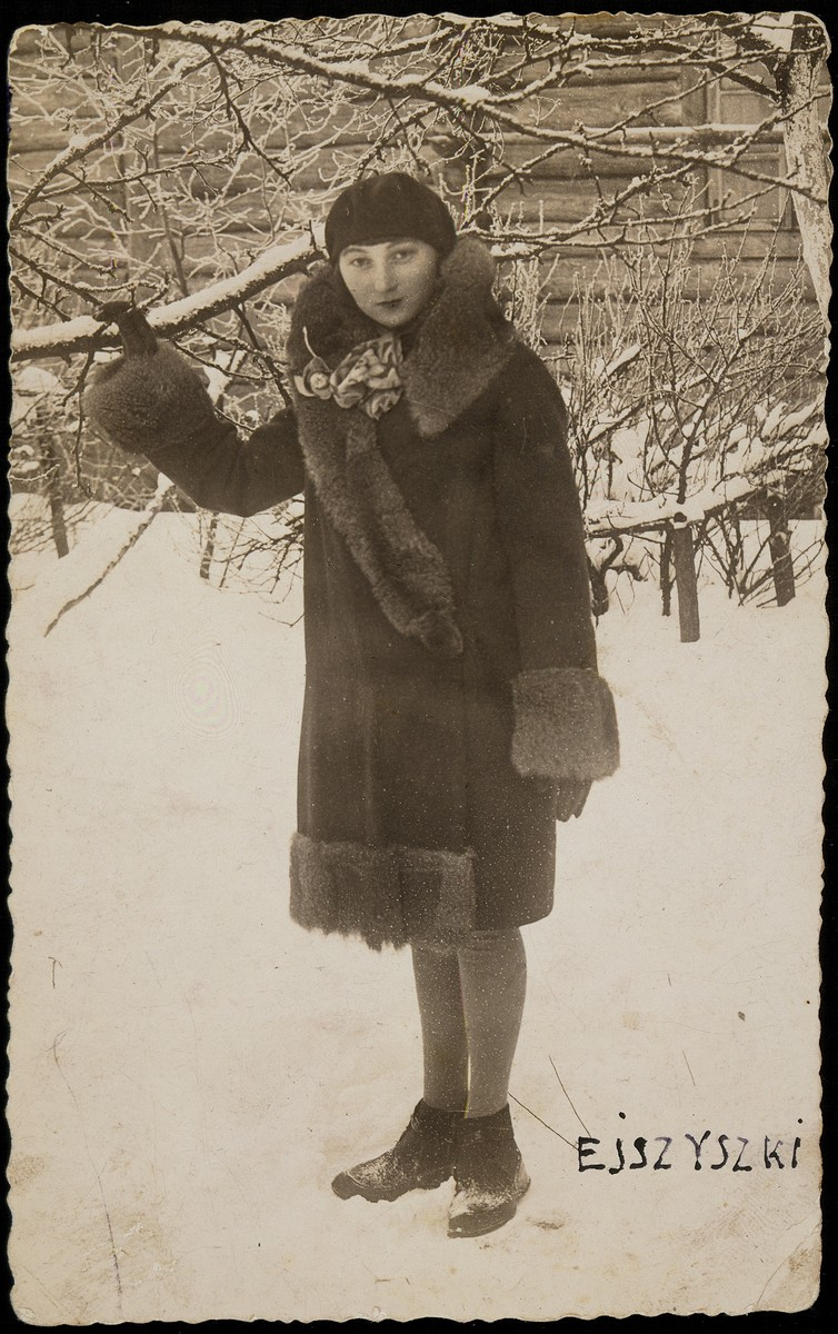 Zipporah (Katz) Sonenson stands in the snow holding onto a tree branch in Eisiskes.